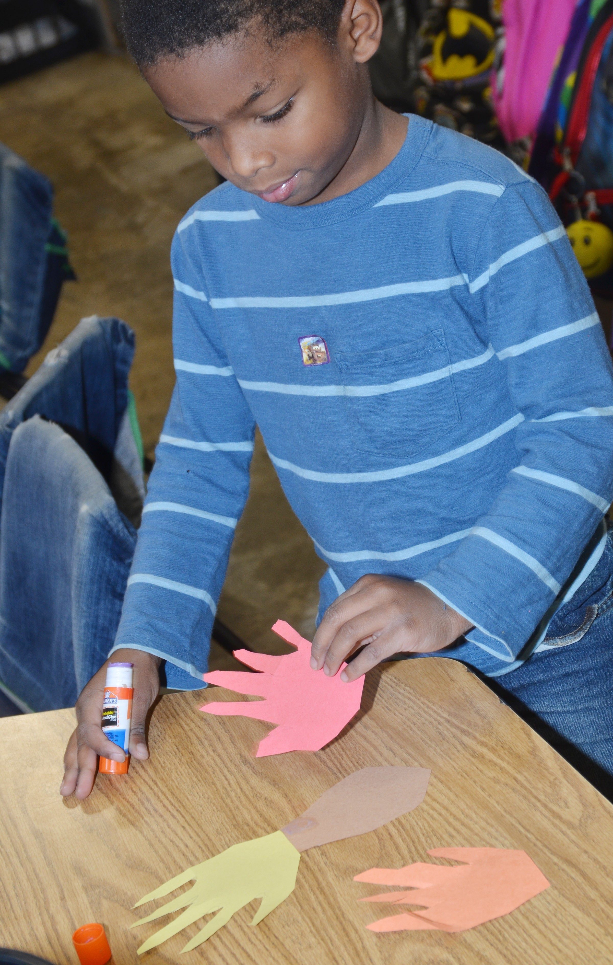 CES kindergartener Kaiyden Vancleave glues his hands together as he makes a turkey.