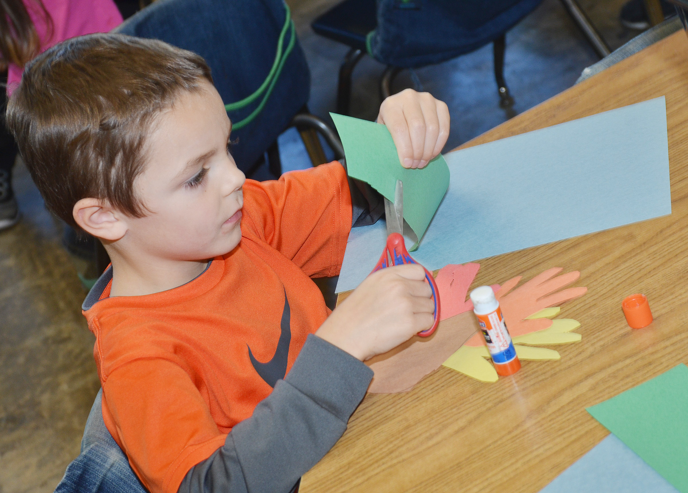 CES kindergartener Hayden Goff cuts out his hands as he makes his turkey.