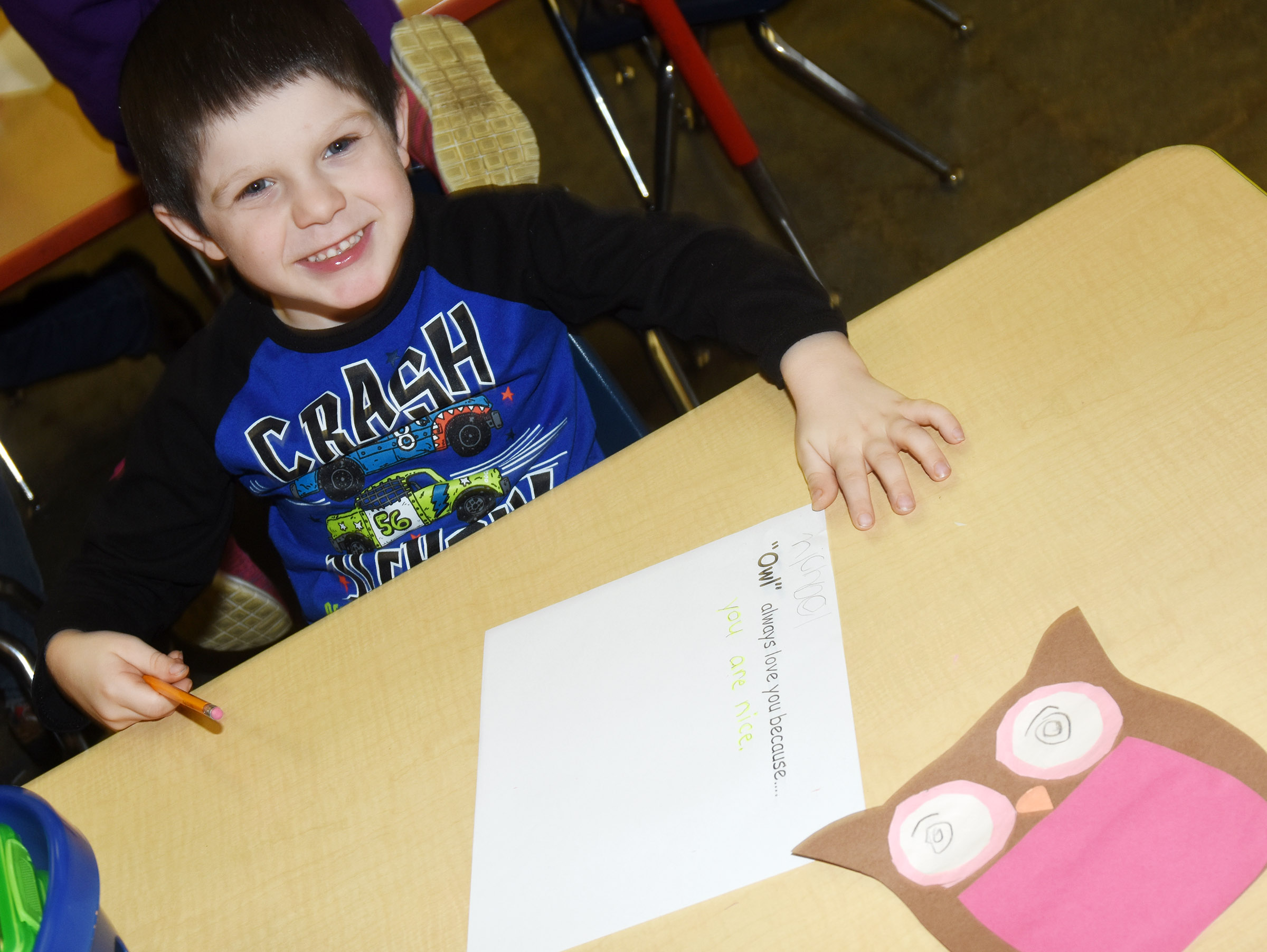 CES kindergartener Michael Priddy smiles as he finishes his Valentine writing.