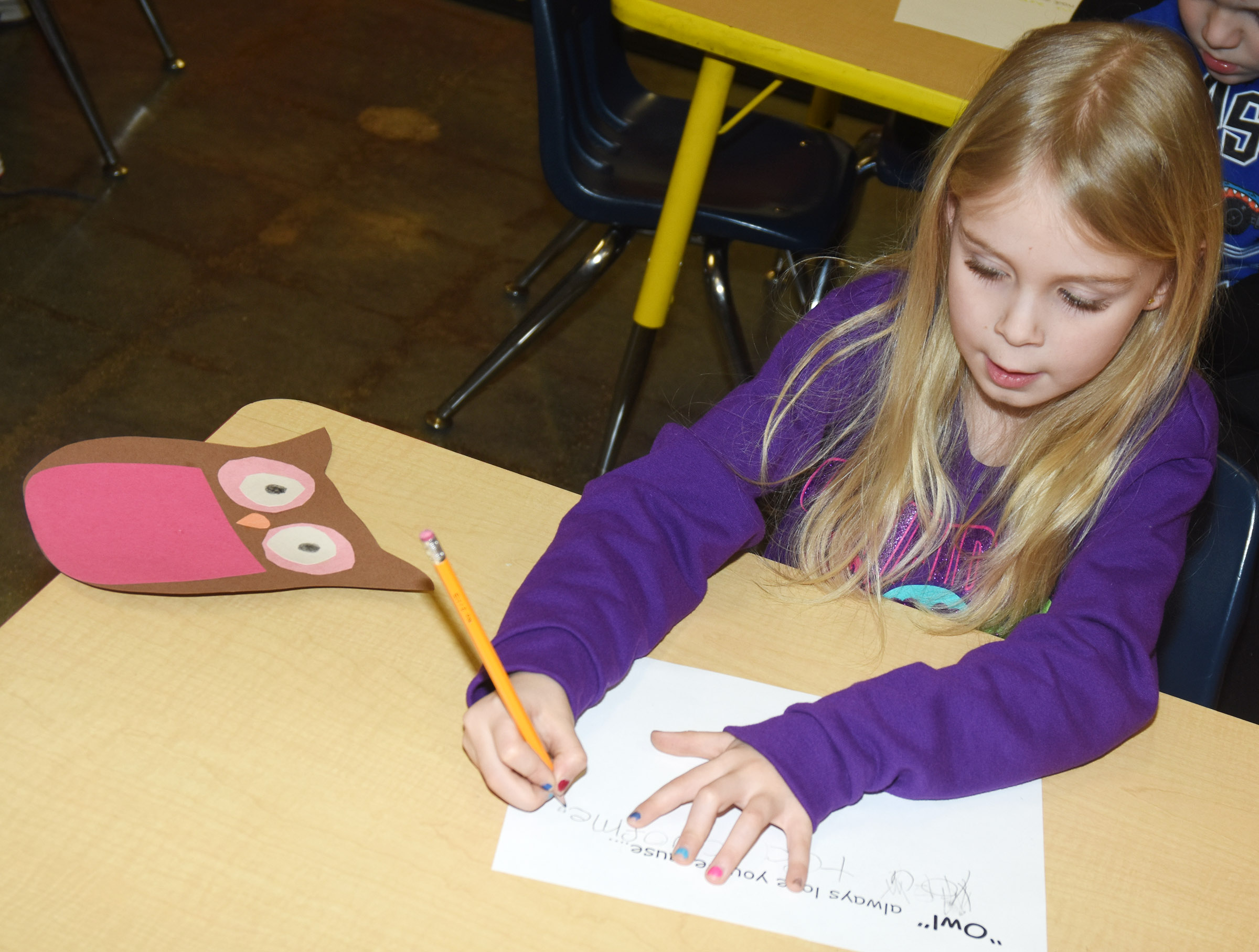 CES kindergarteners Alinna Bray finishes her Valentine writing.