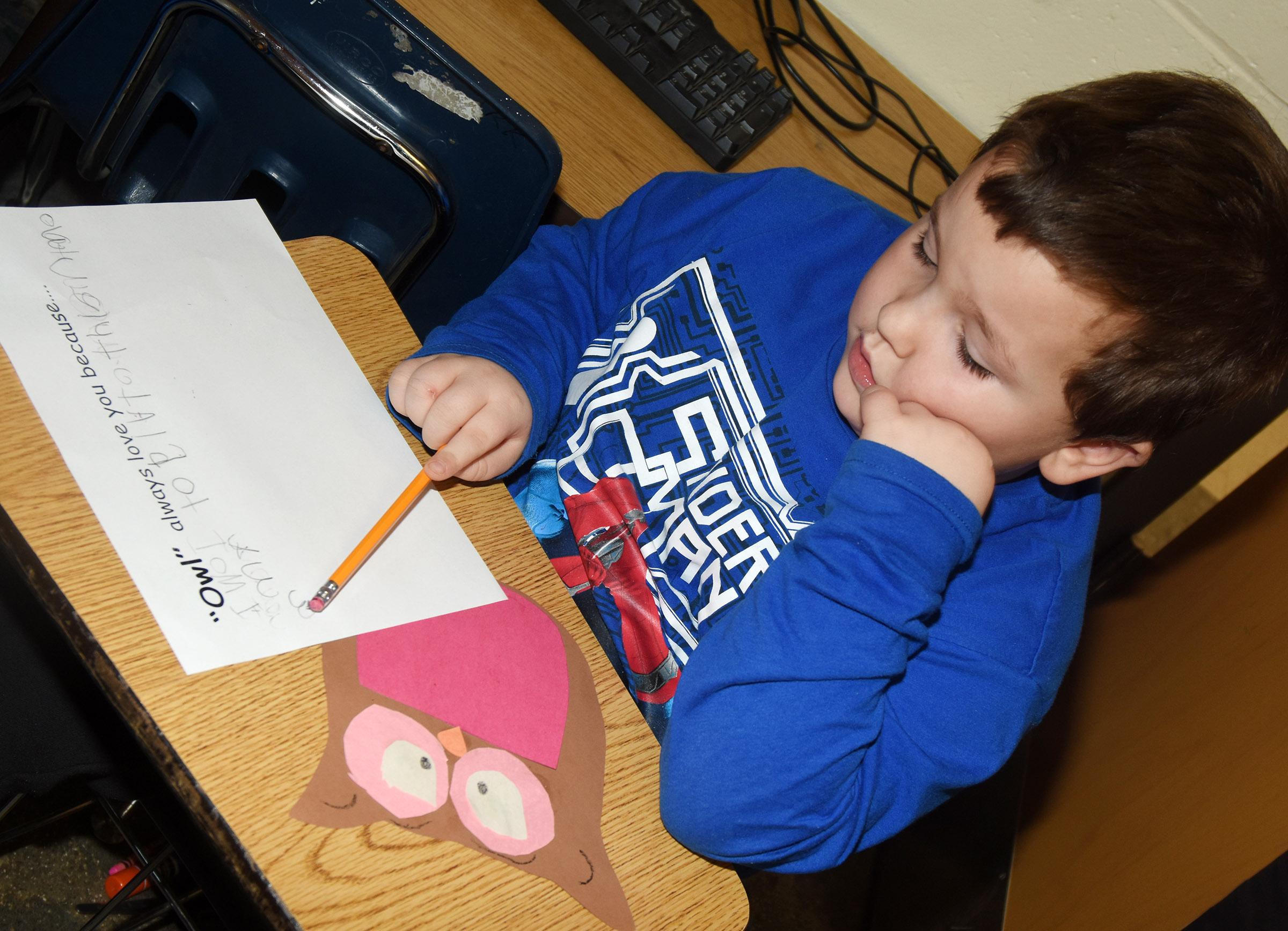 CES kindergartener Mason Gribbin finishes his Valentine writing.