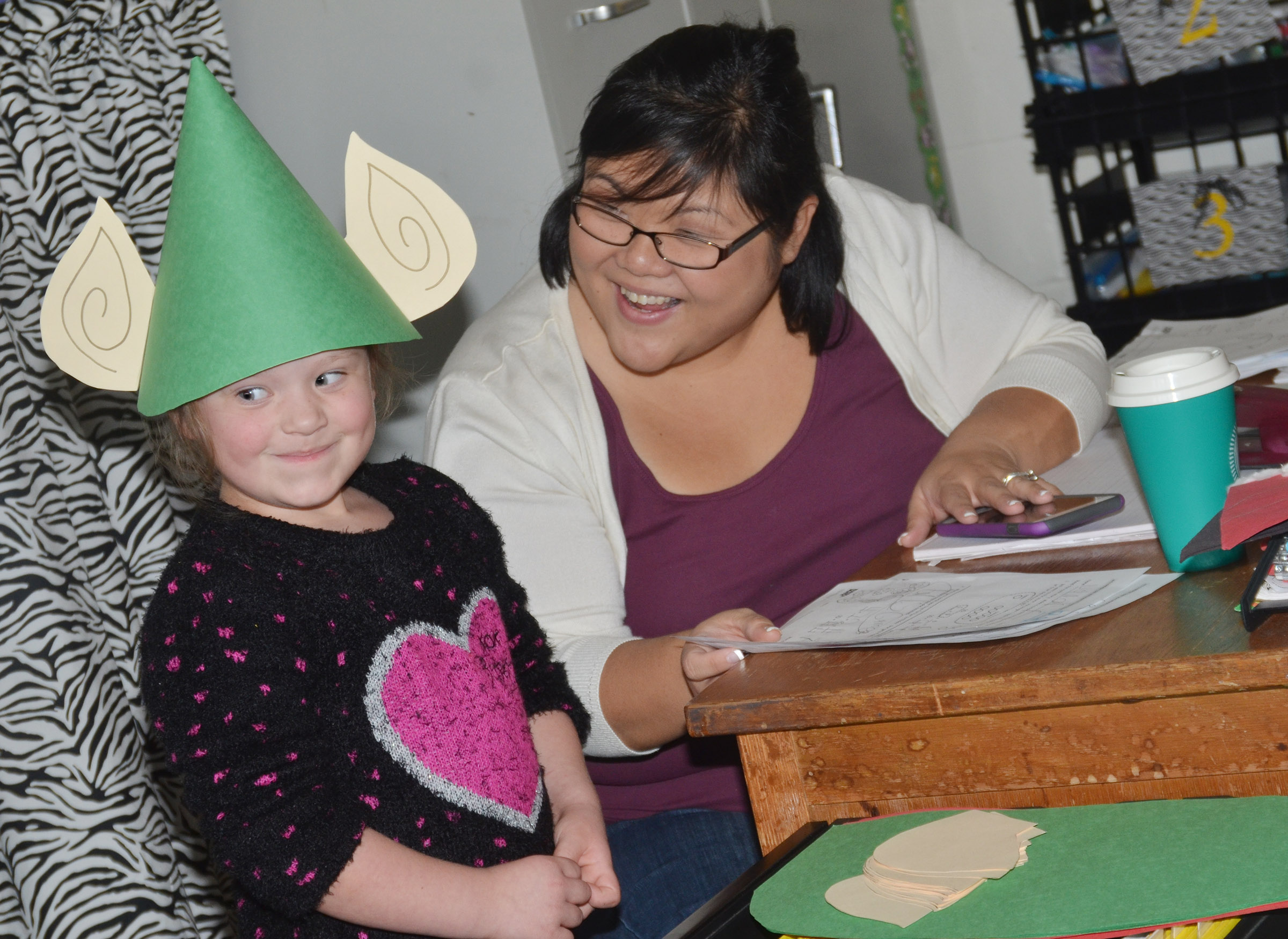 CES kindergarten assistant Brittany Johnson smiles as Gracie McKenzie tries on her elf hat.