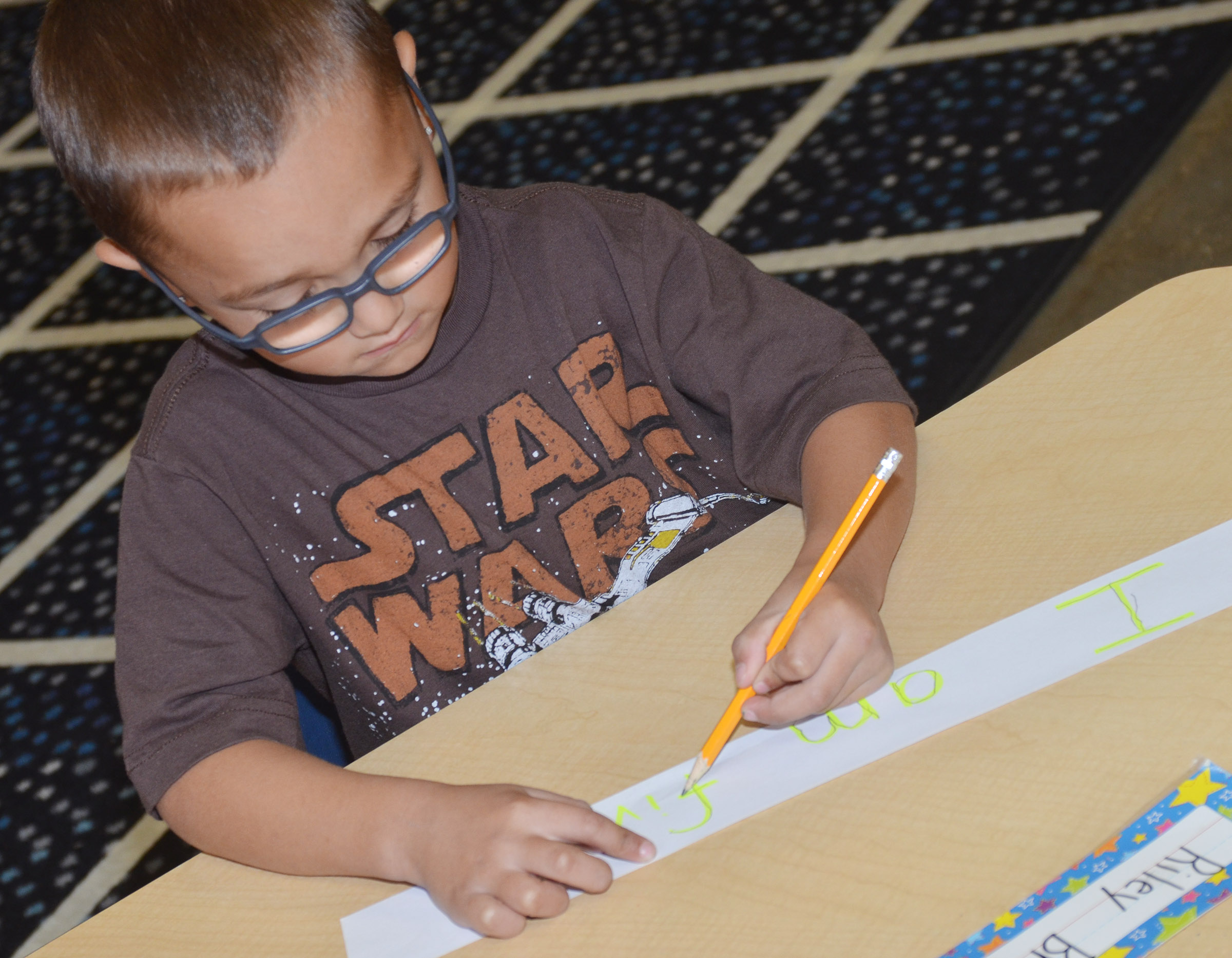 CES kindergartener Chanler Mann practices writing a sentence.