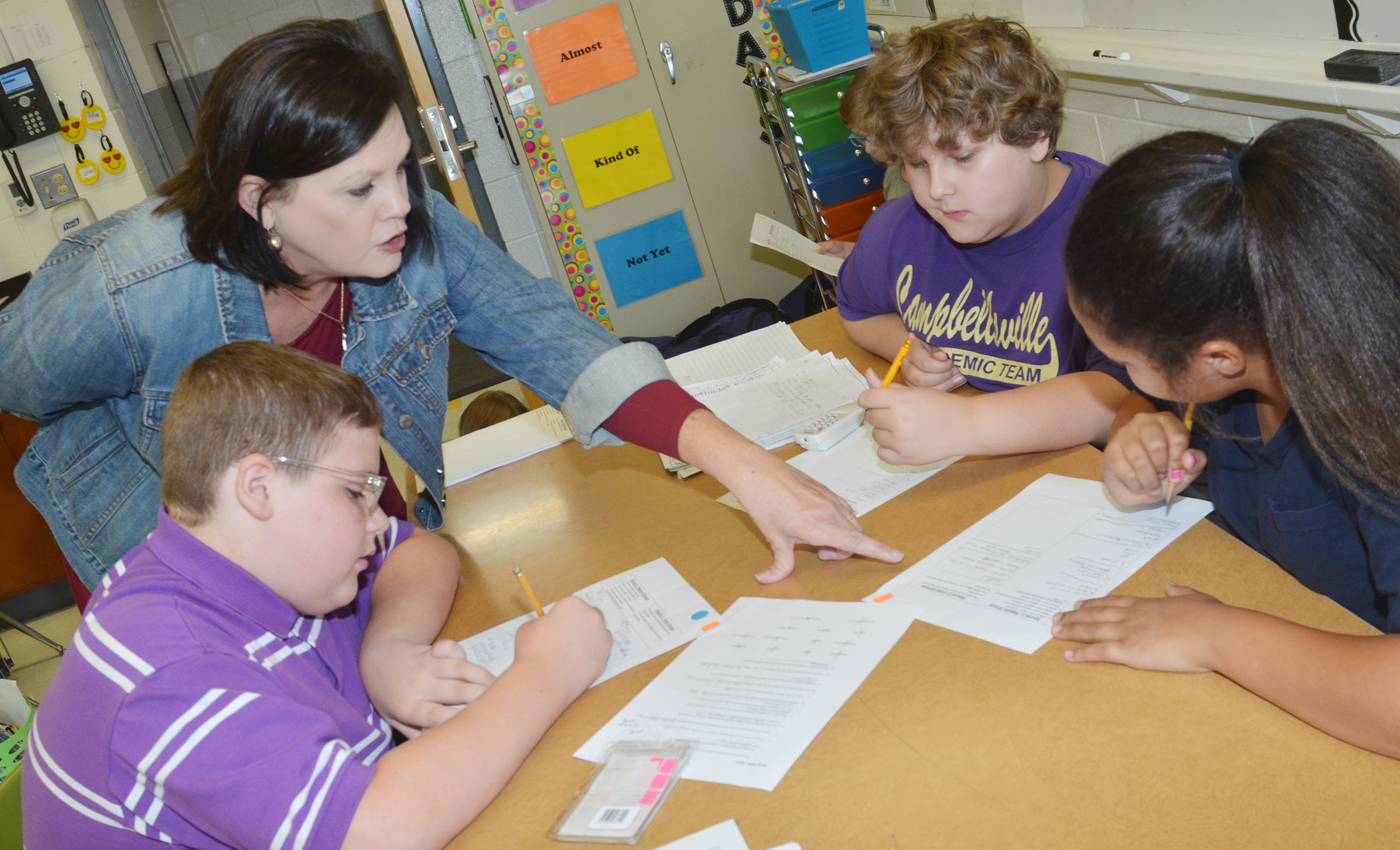 CES fifth-grade teacher Lisa Kearney talks to her students, from left, Ian Creason, Zeke Harris and Kenya Bridgewater.