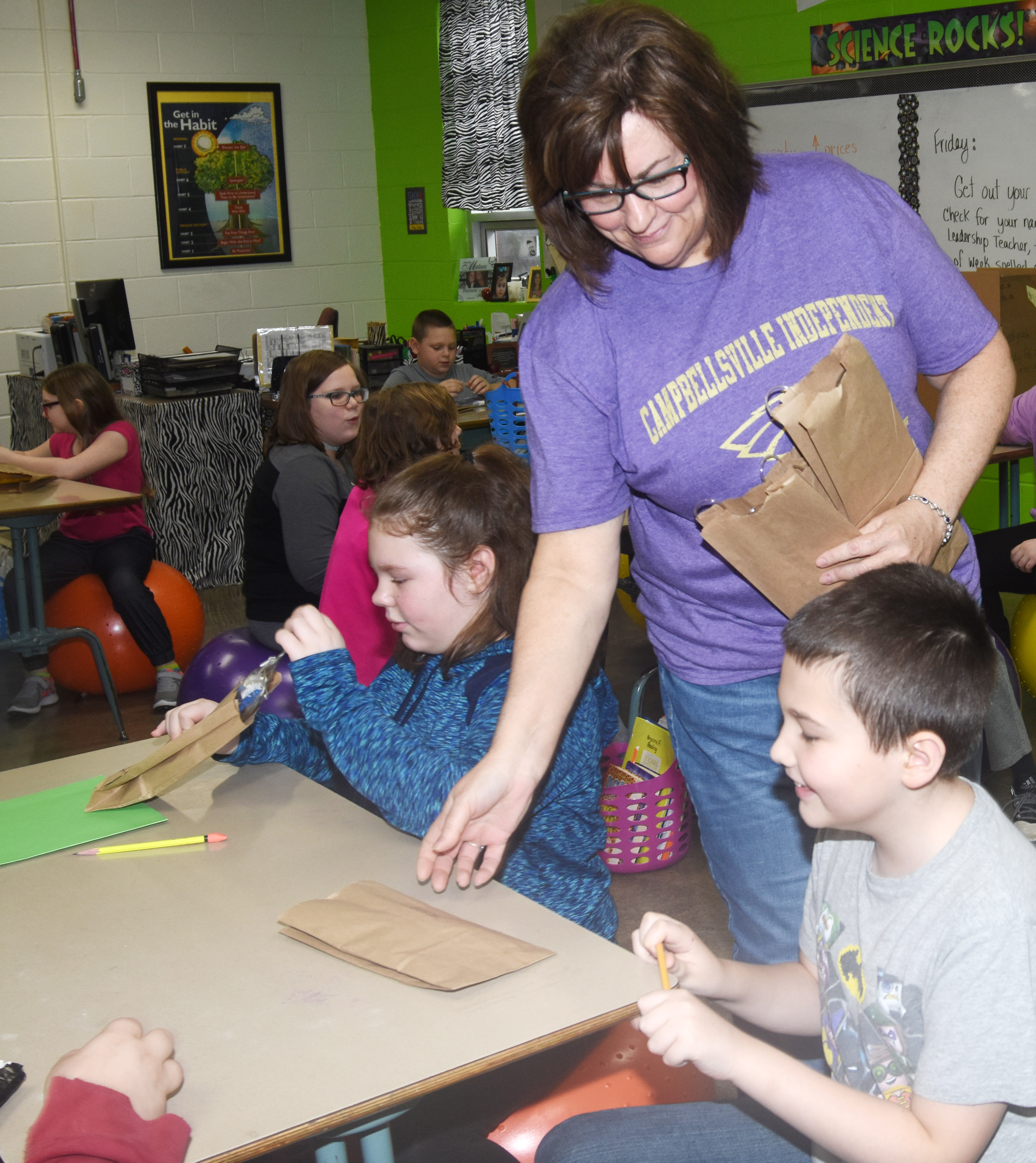 Susan Kennon, a Campbellsville Family Resource and Youth Services Center liaison at CES, passes out toothbrushes to fifth-grade students.