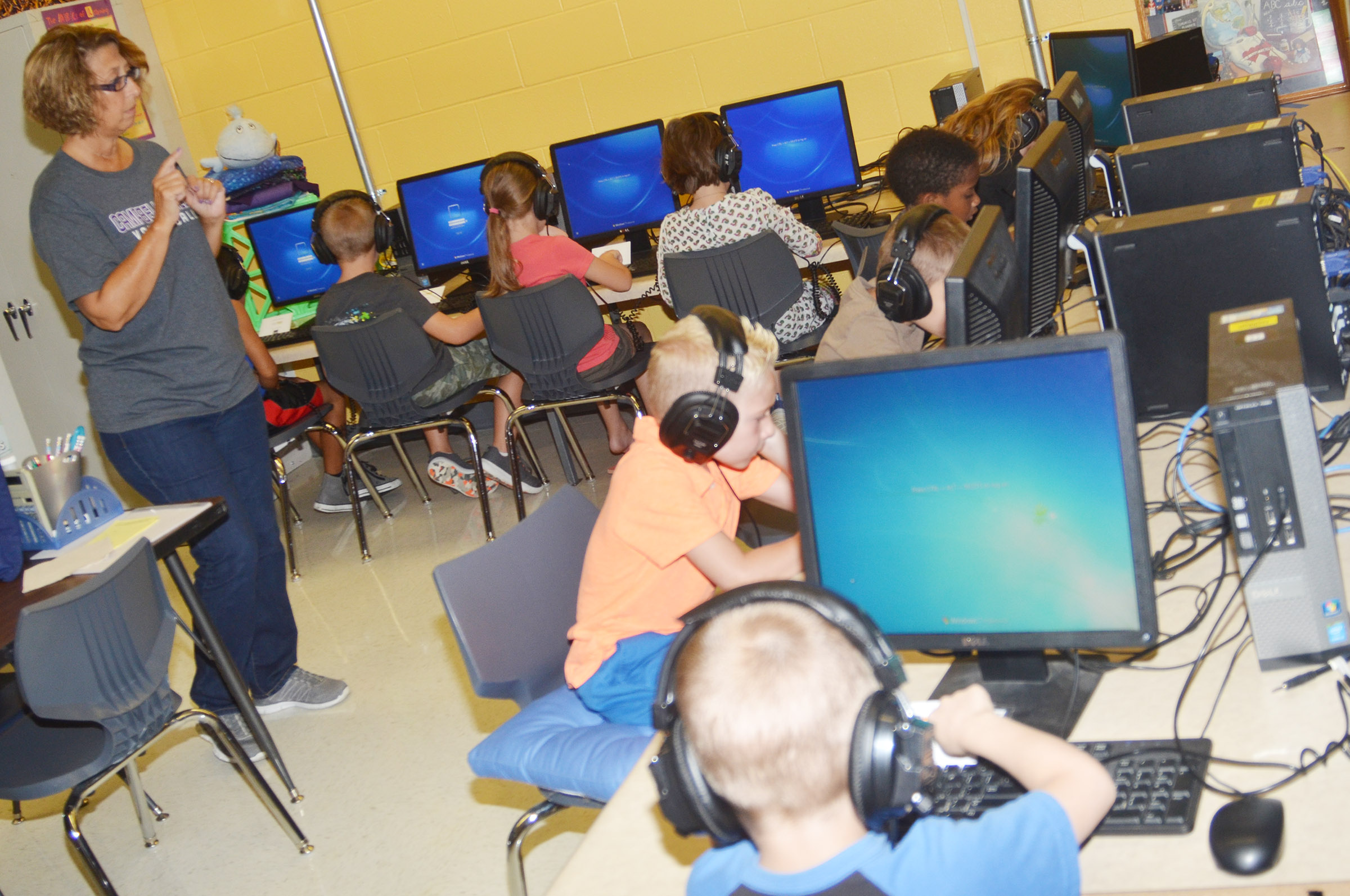CES teacher Beverly Knifley tells first-graders how to log on their computer.