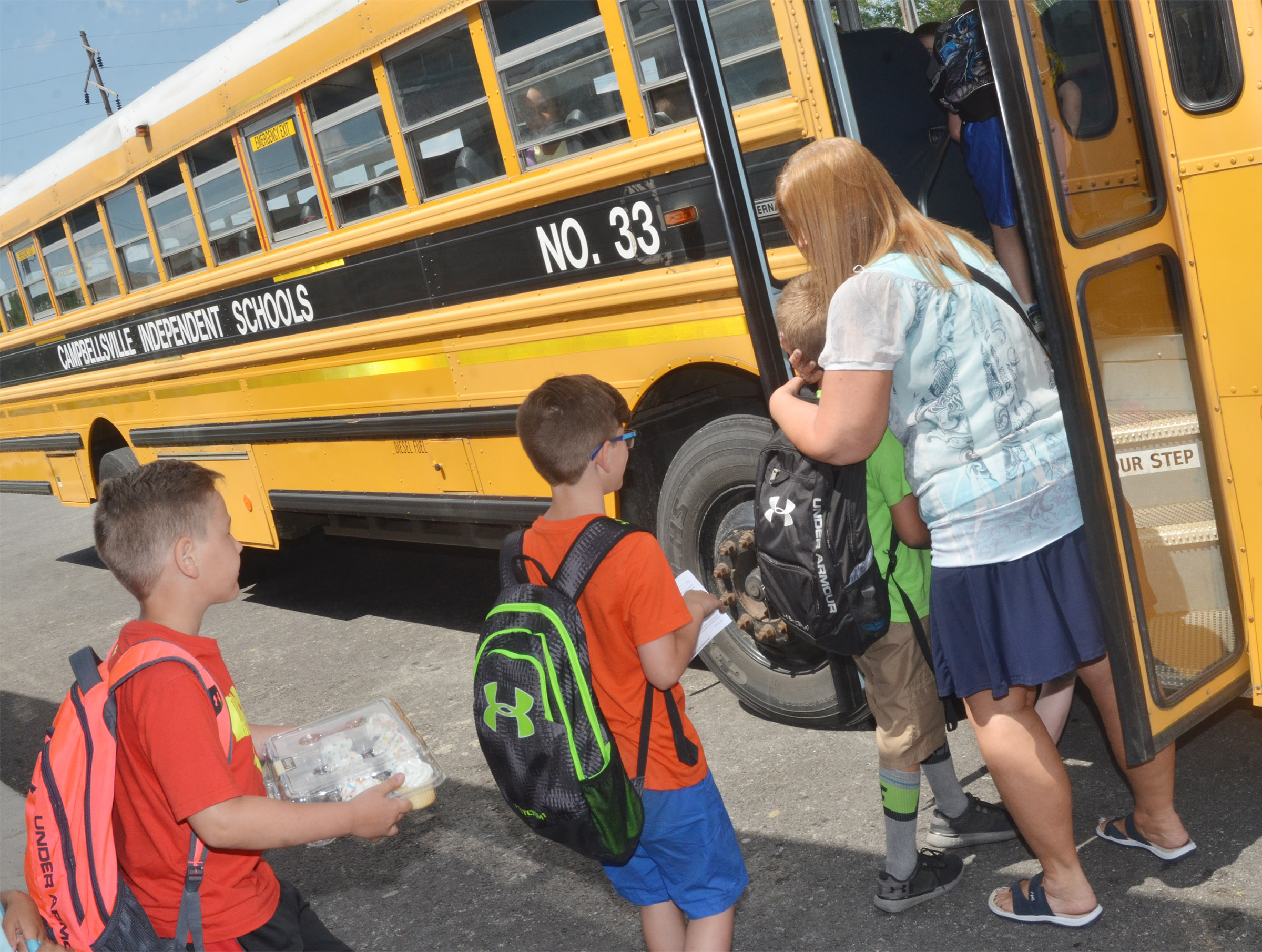 CES students say goodbye to teacher Jane Parrott as they board the bus.
