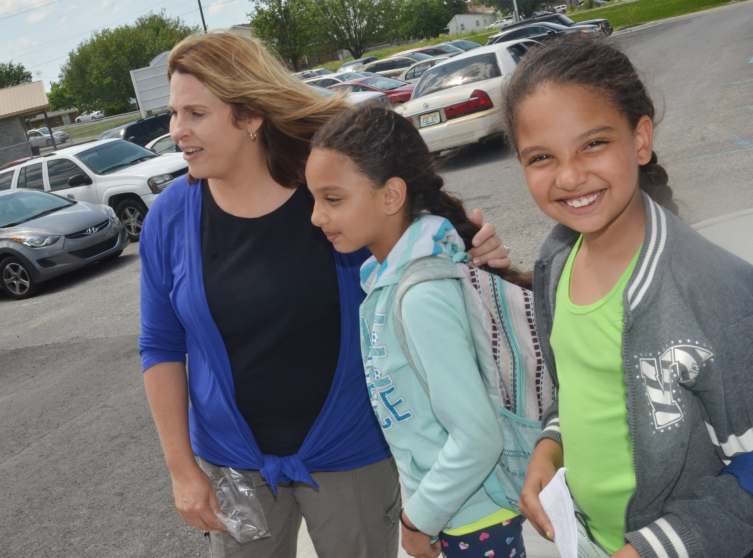 CES Guidance Counselor waits with third-graders Alyssa Knezevic, at left, and her sister Aleecia, as their mother picks them up from school.
