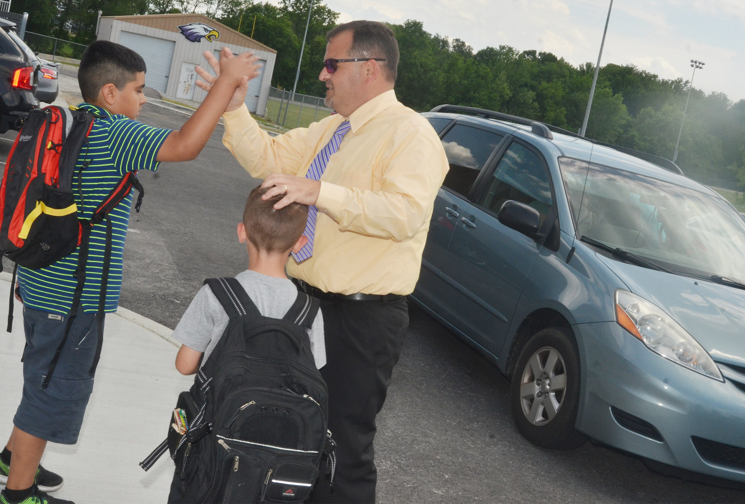 CES Principal Ricky Hunt high fives third-grader Cody Tamez as he leaves school.