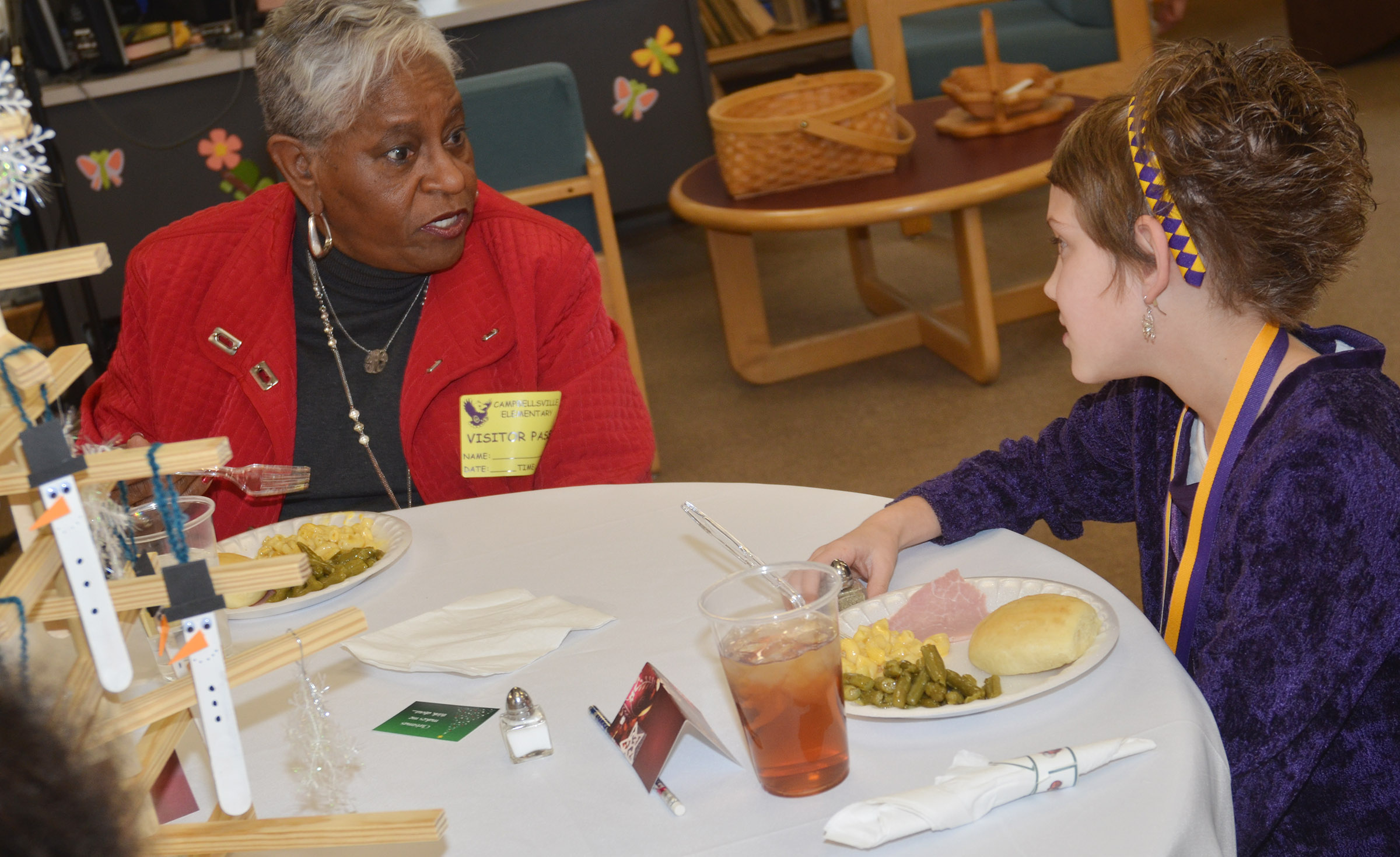 Yvette Haskins, a community leader, has lunch with CES second-grader Baylee Pike.