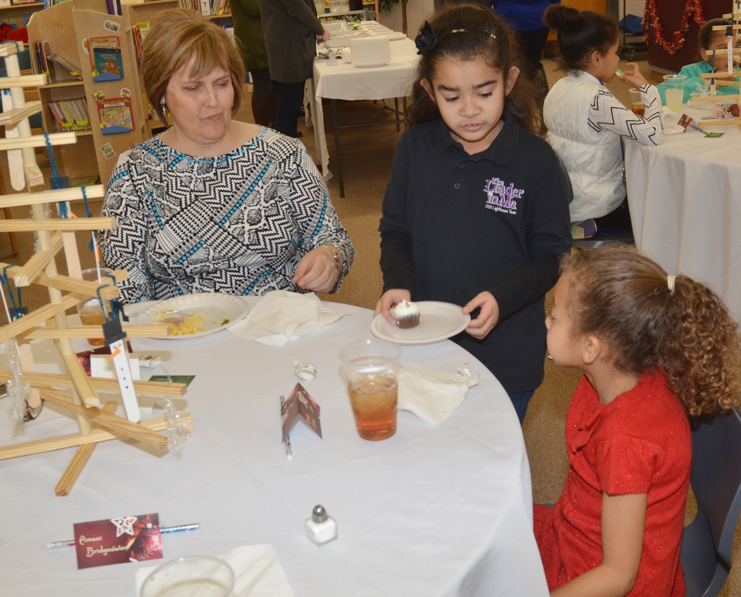Retired teacher Debbie Edwards has lunch with CES first-grader Londyn Smith, as second-grader Sophia Santos serves dessert.