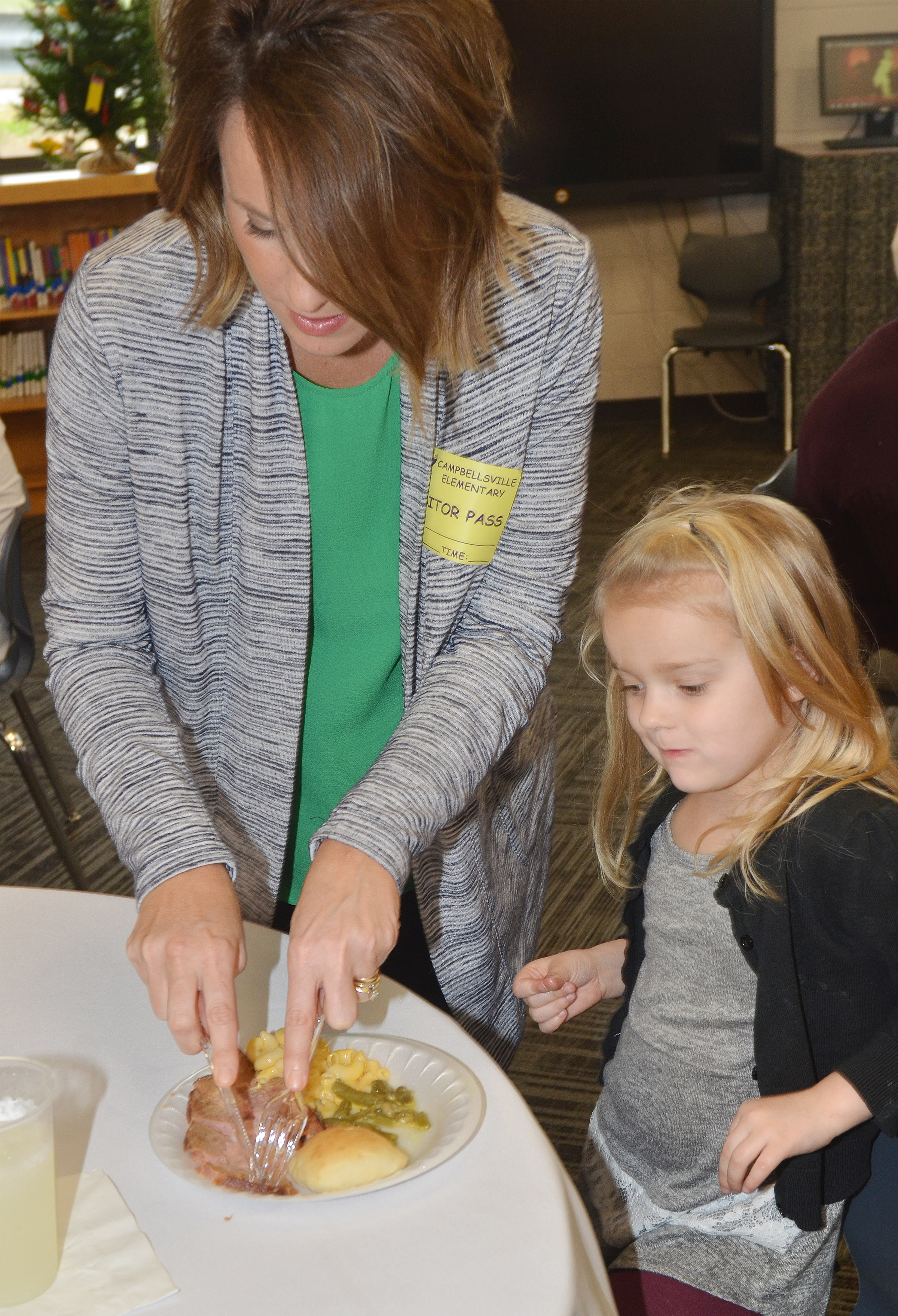 Paige Hord, owner of The Green Room, cuts kindergartener Miley Orberson's meat.