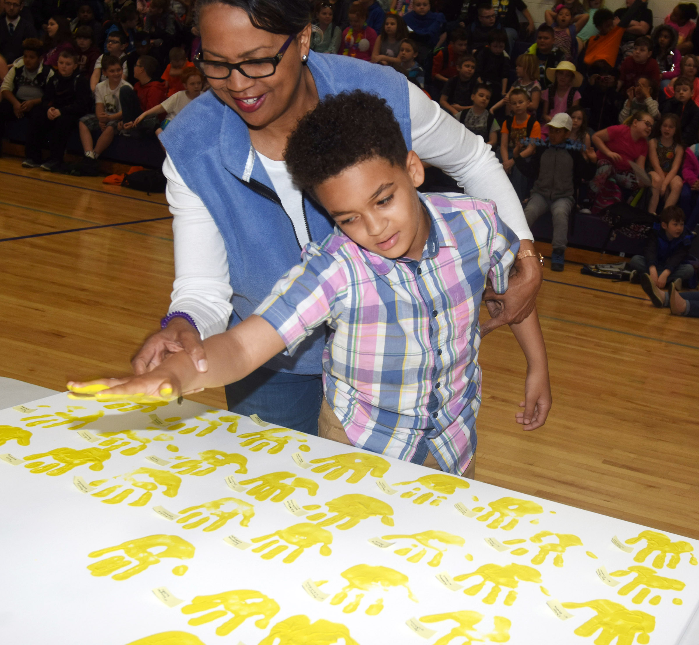 CES fourth-grader Jaden Barbee places his handprint on the canvas, with help from Assistant Principal Doretha Sanders.
