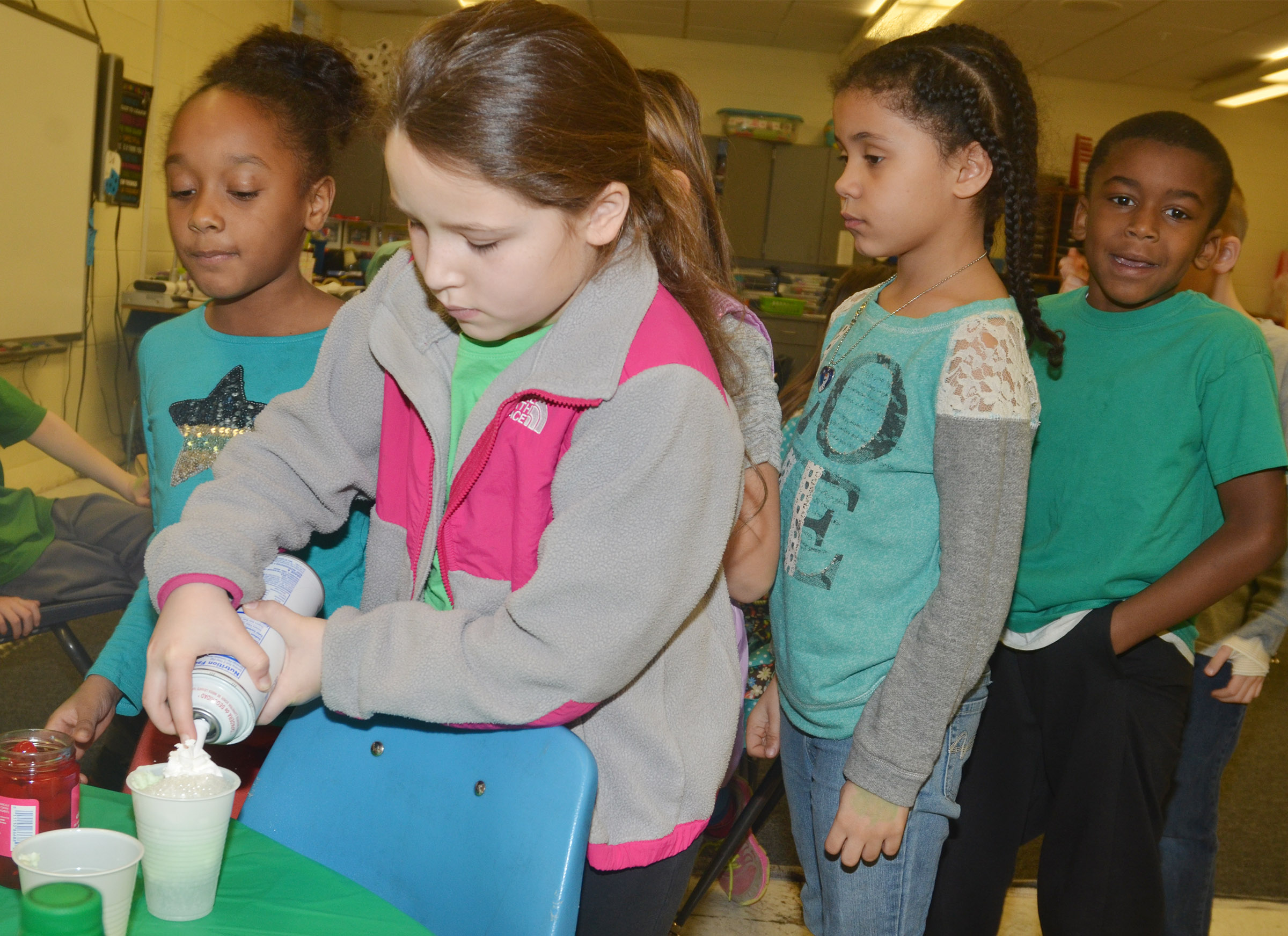 CES second-grader Keely Rakes adds whipped cream to her leprechaun float as her classmates wait to make theirs.