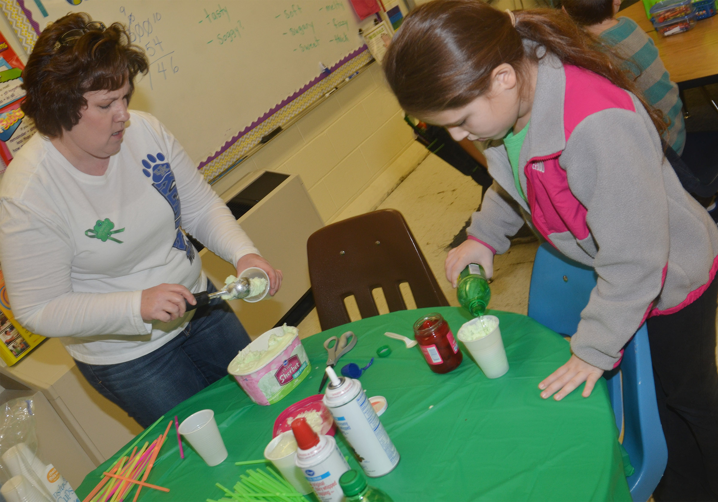 CES second-grade teacher Tracey Rinehart scoops sherbet as Keely Rakes adds soda to her leprechaun float.
