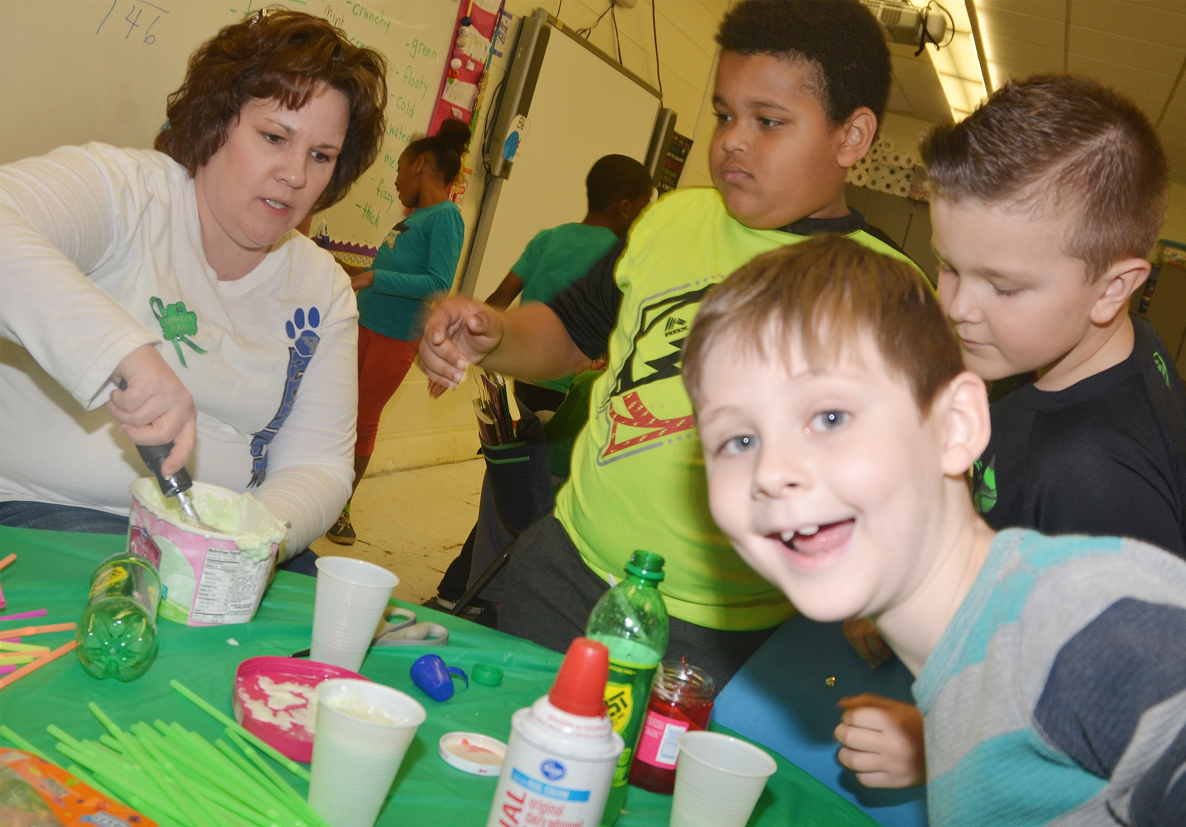 CES second-grader Ryan Tungate smiles as he waits to make his leprechaun float. At left, teacher Tracey Rinehart helps Jayden Moore and Cayton Lawhorn make their floats.