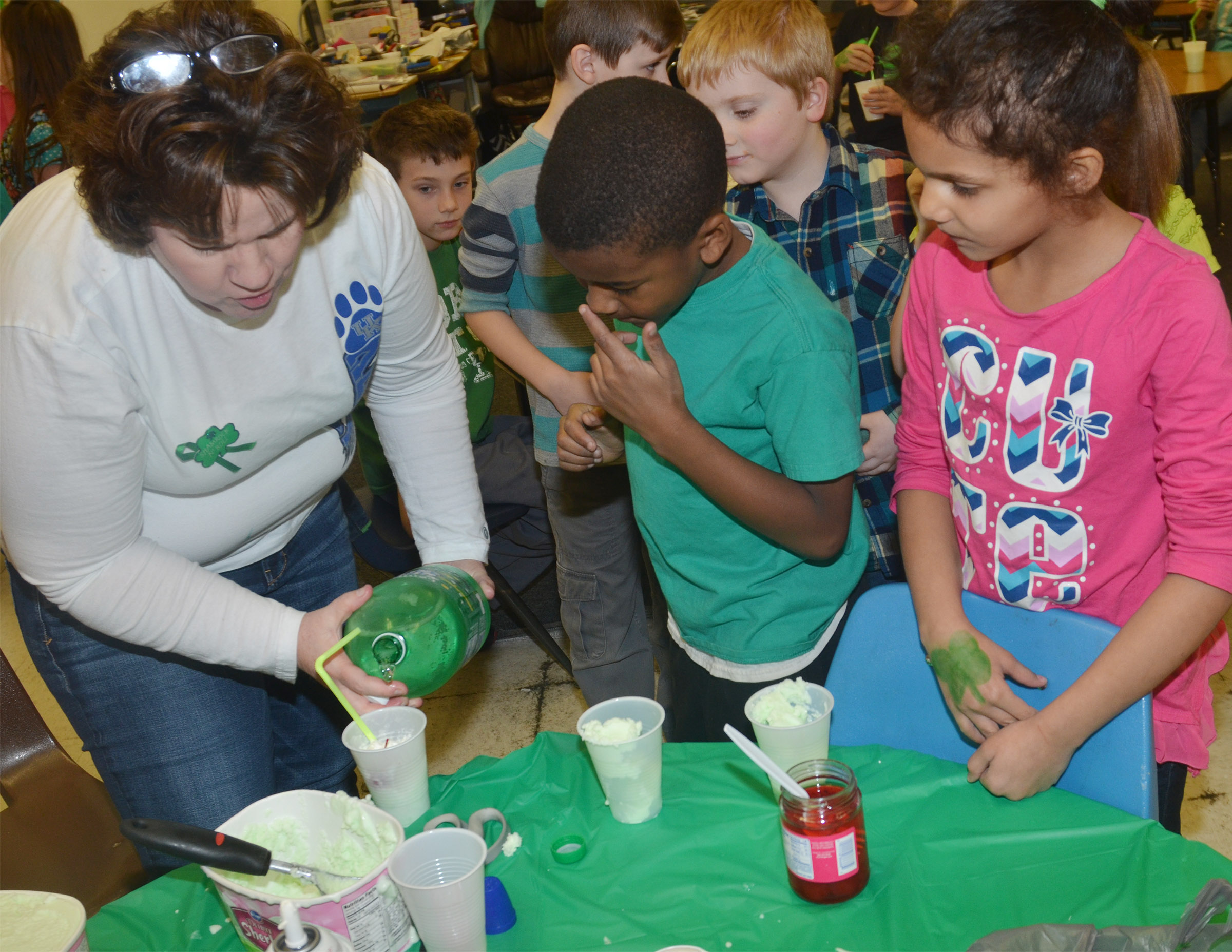 CES second-grade teacher Tracey Rinehart helps Kae'vin Spaulding, center, and Malia Thompson make their leprechaun floats.