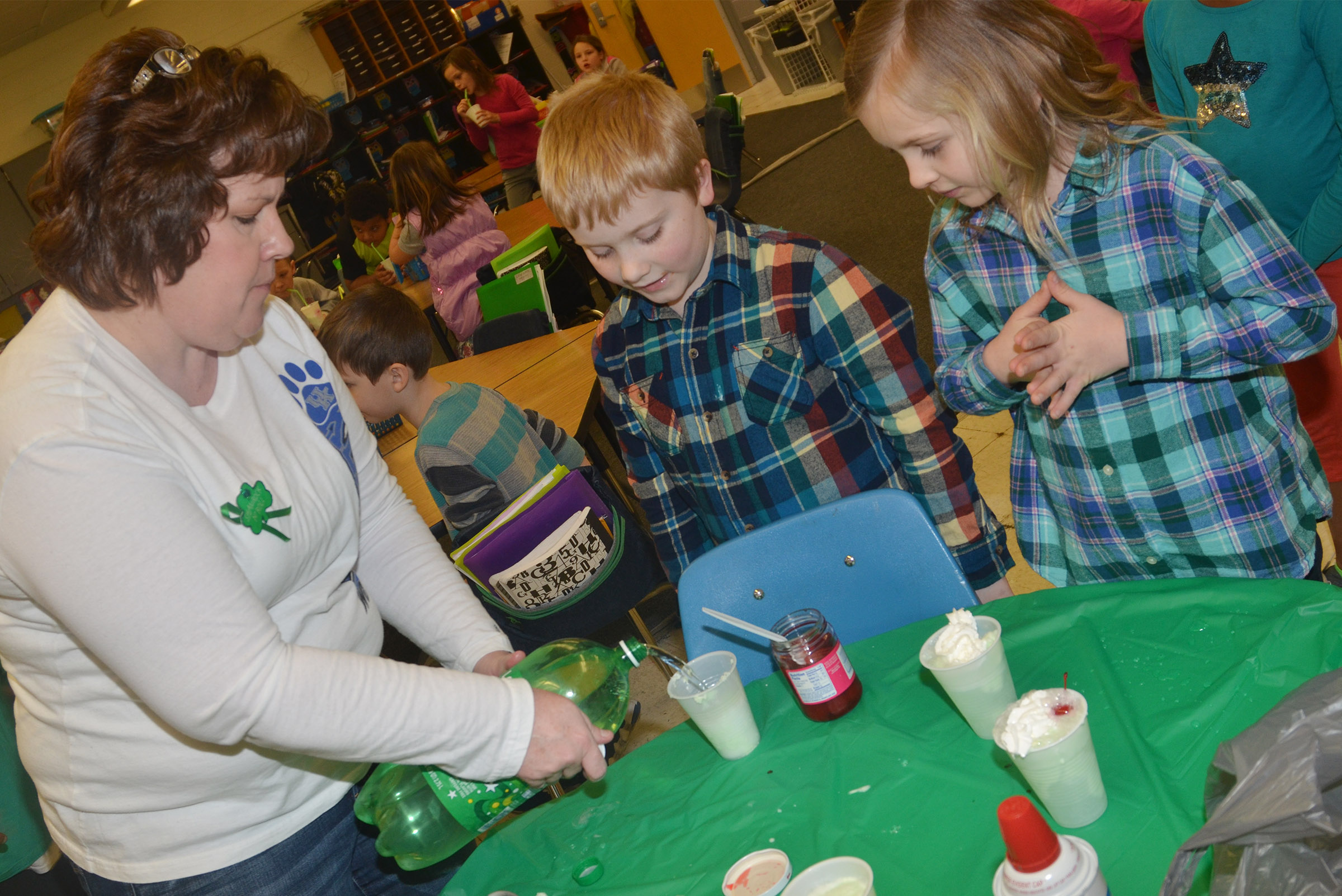 CES second-grade teacher Tracey Rinehart helps Aidan Bowles, center, and Ava Ellis make their leprechaun floats.