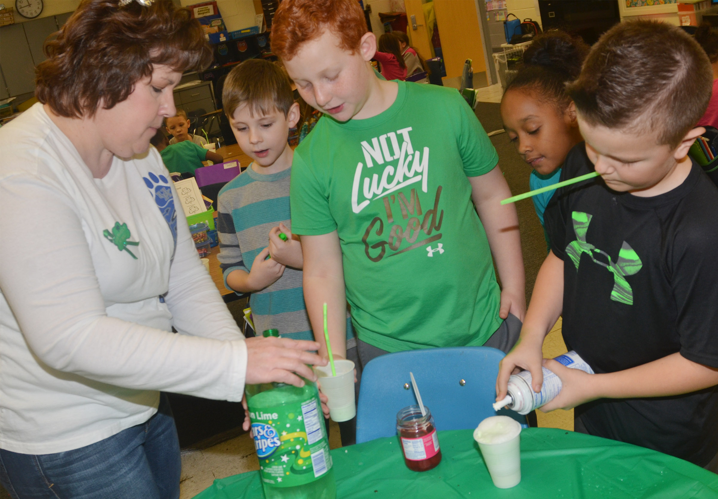 CES second-grade teacher Tracey Rinehart helps, from left, Ryan Tungate, Spencer Swafford, Lashonda Wilkinson and Cayton Lawhorn make their leprechaun floats.