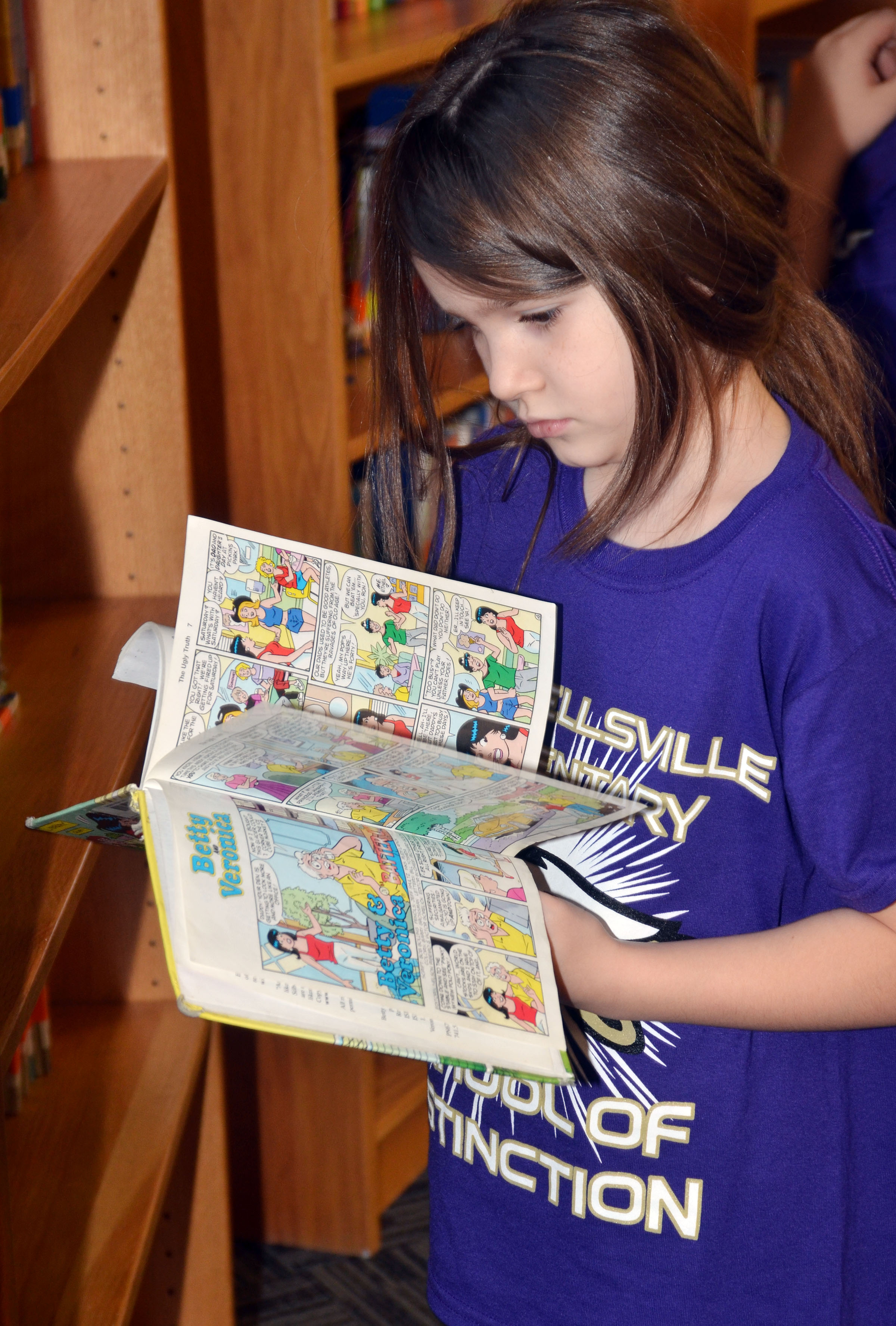 CES third-grader Destiny Abell looks through a comic book at the library.