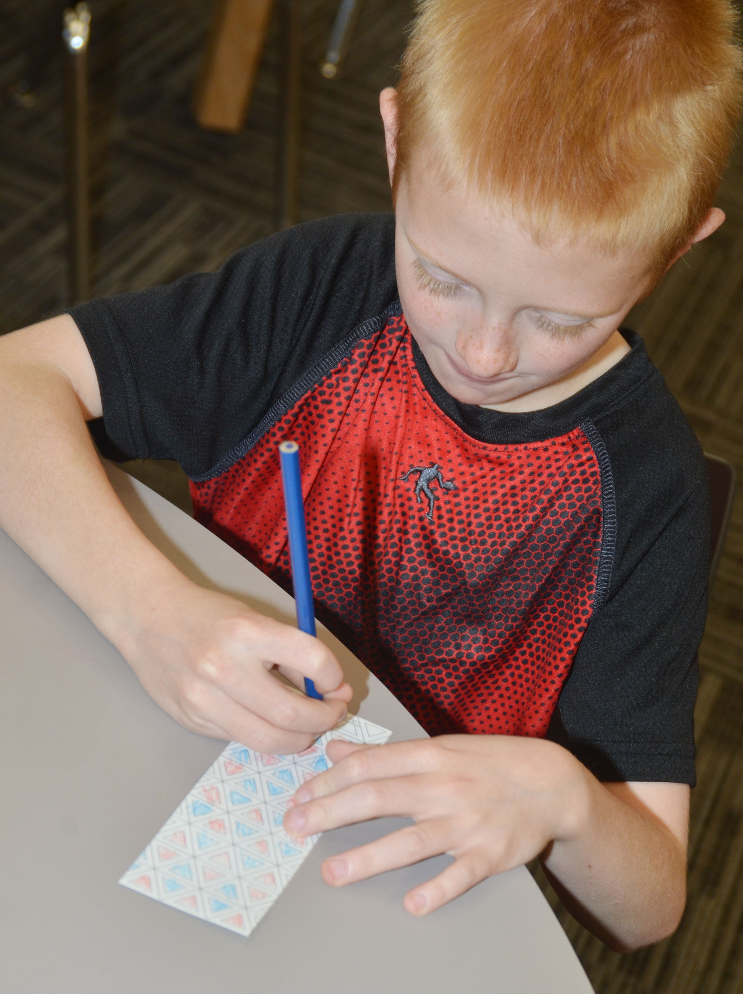 CES first-grader Jacob Wethington colors a bookmark at the library.