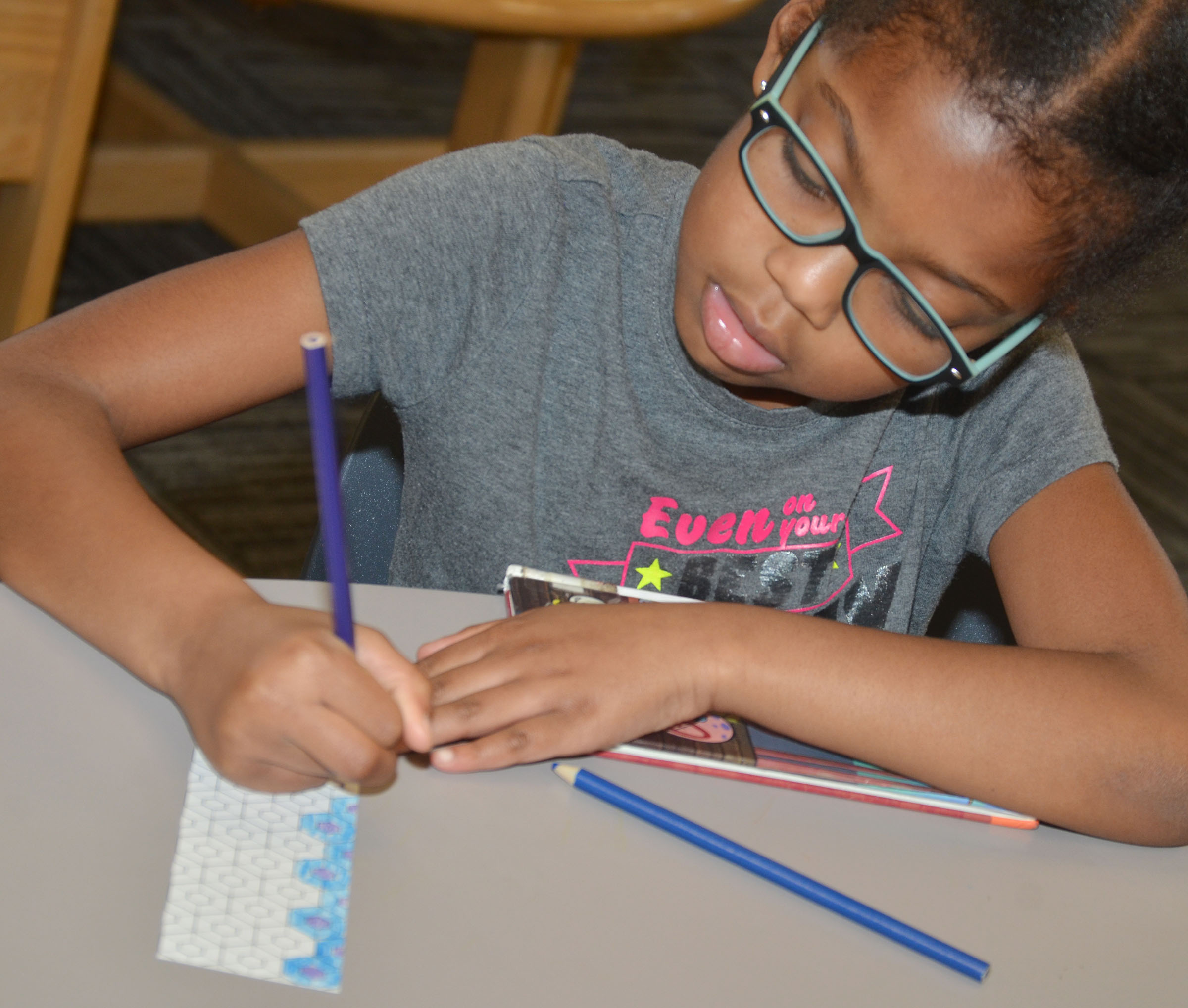 CES first-grader Willow Griffin colors a bookmark at the library.