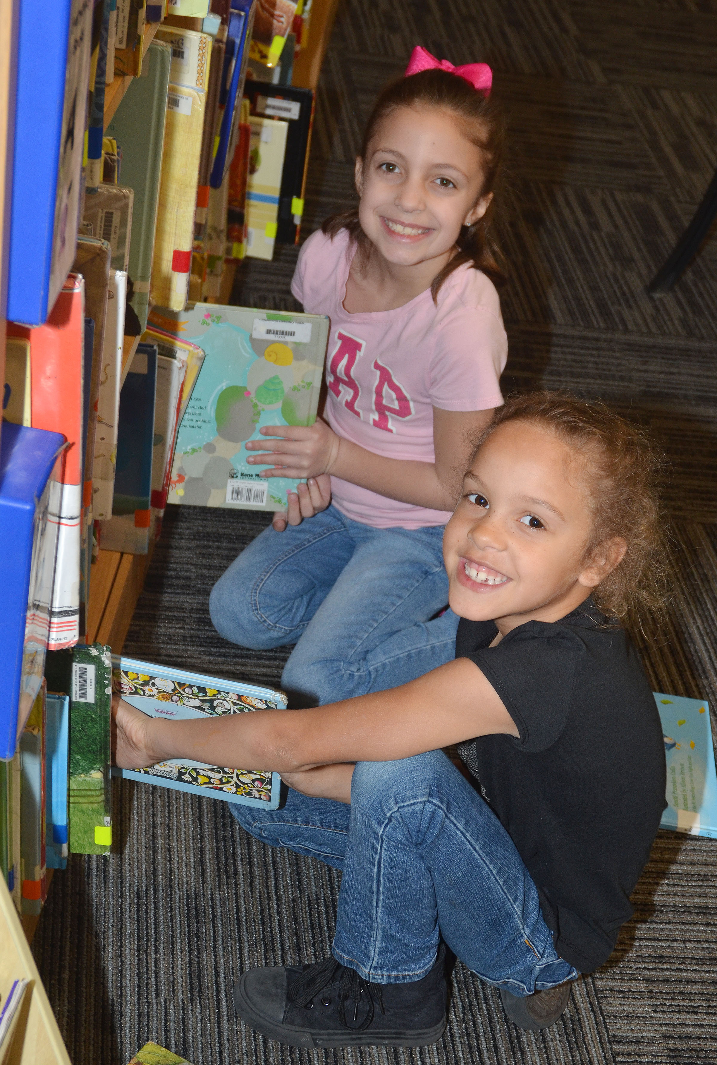 CES first-graders Lillian Martin, at left, and Keiava Thompson look for books to check out at the library.