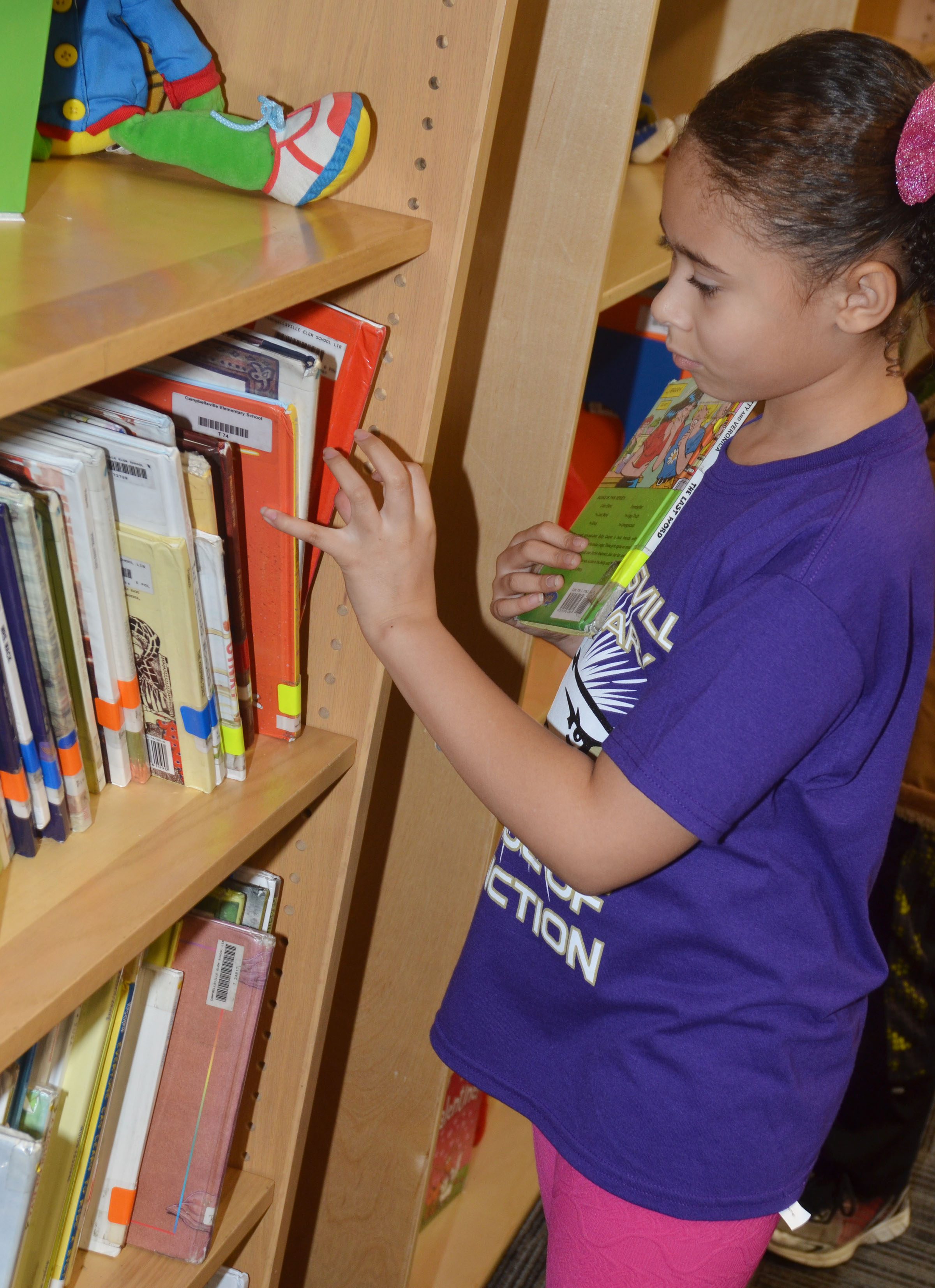 CES third-grader Rihanna Anderson looks for a book to check out at the library.