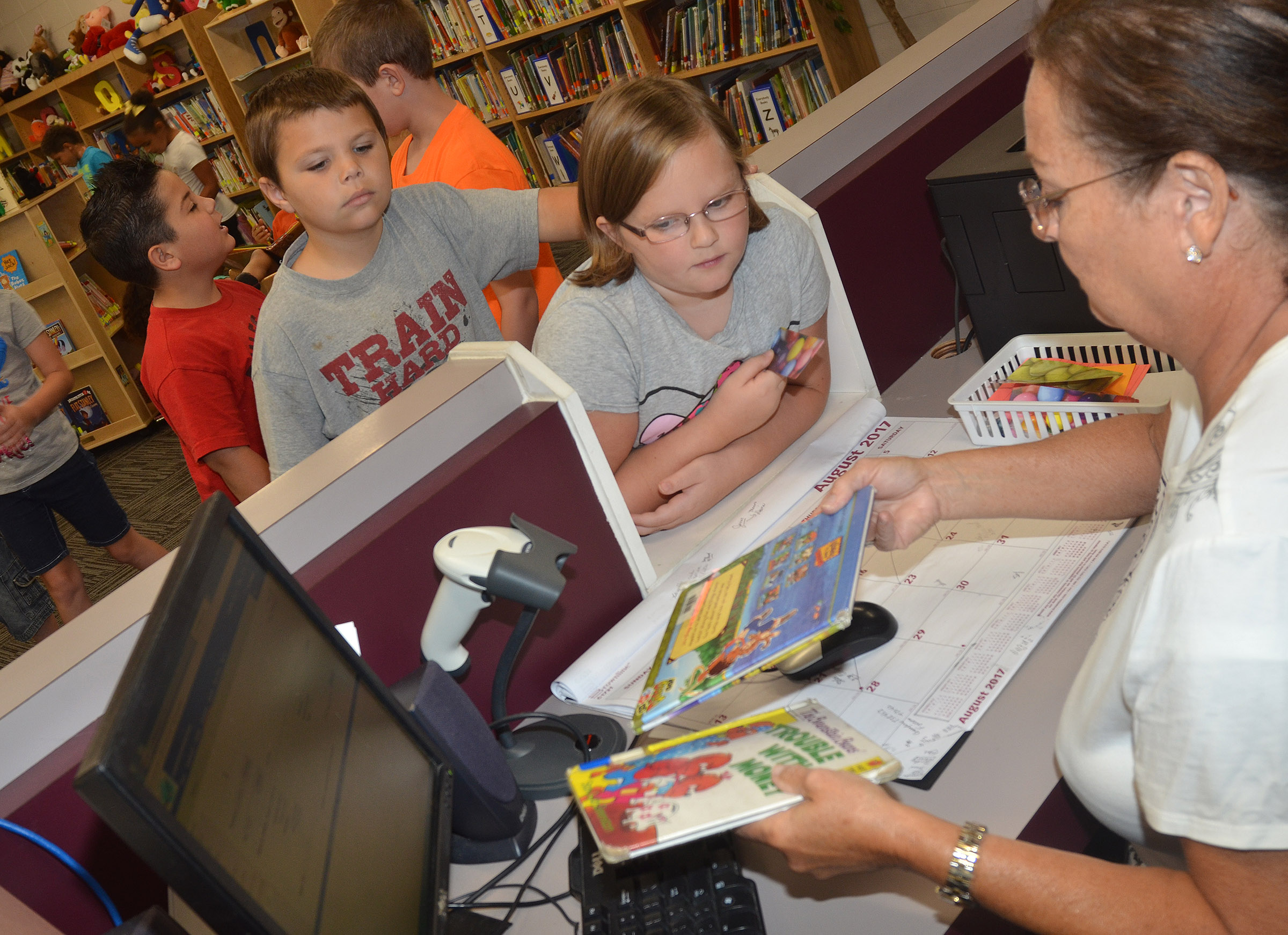 CES library assistant Lois Kemp helps second-grader Justice Albrecht check out a book, as Jaxson Hunt waits his turn.