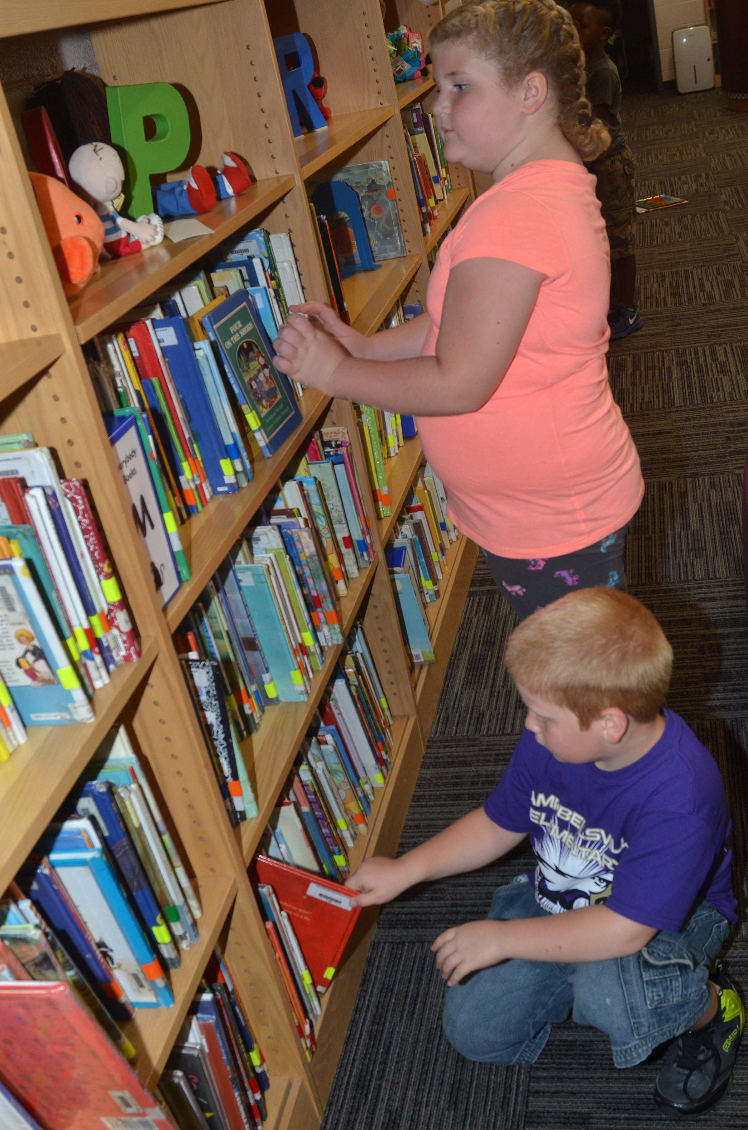 CES second-graders Elizabeth Foster and Ben Parrott look for books in the library.