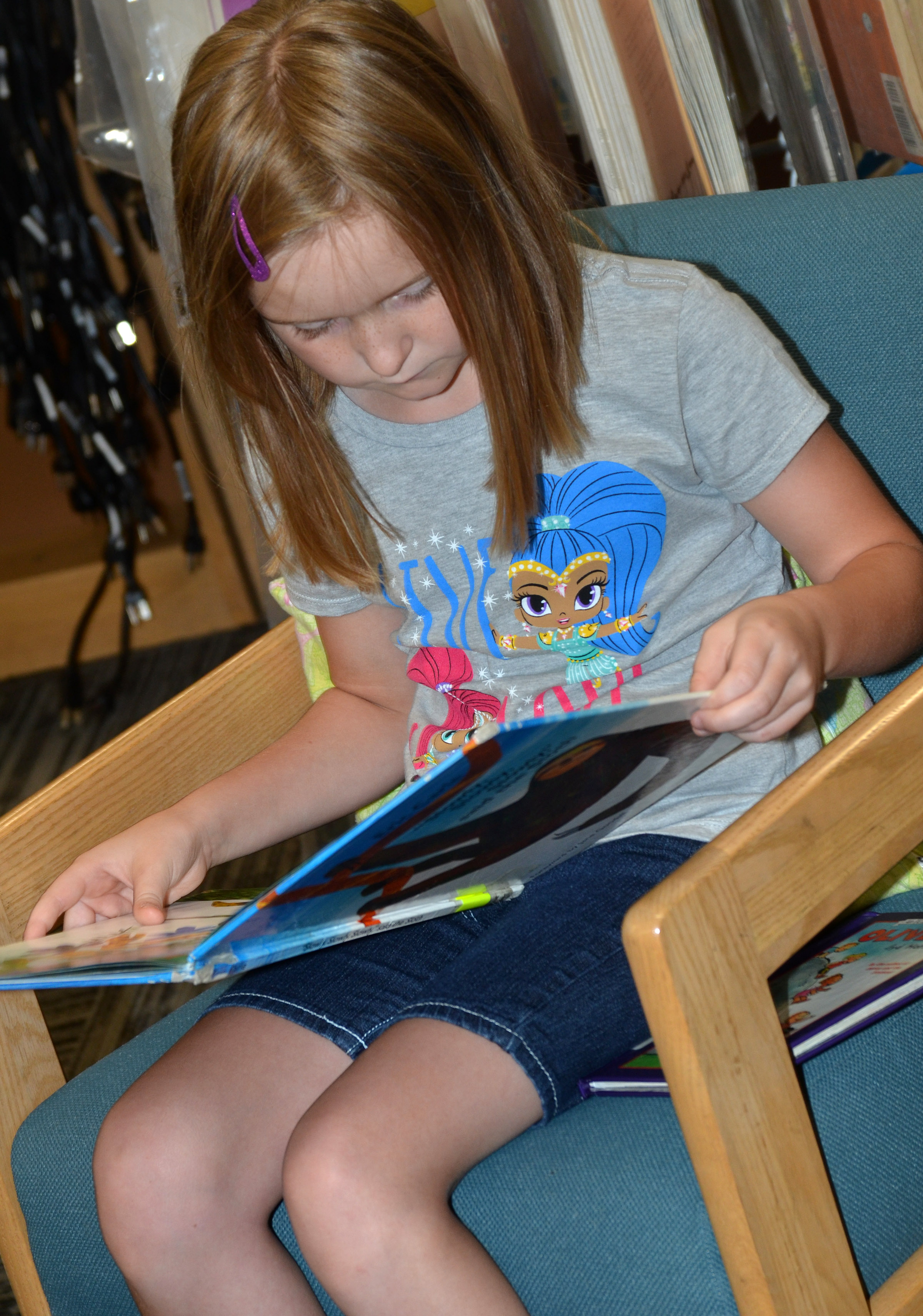 CES second-grader Gracie Murphy reads a book at the library.