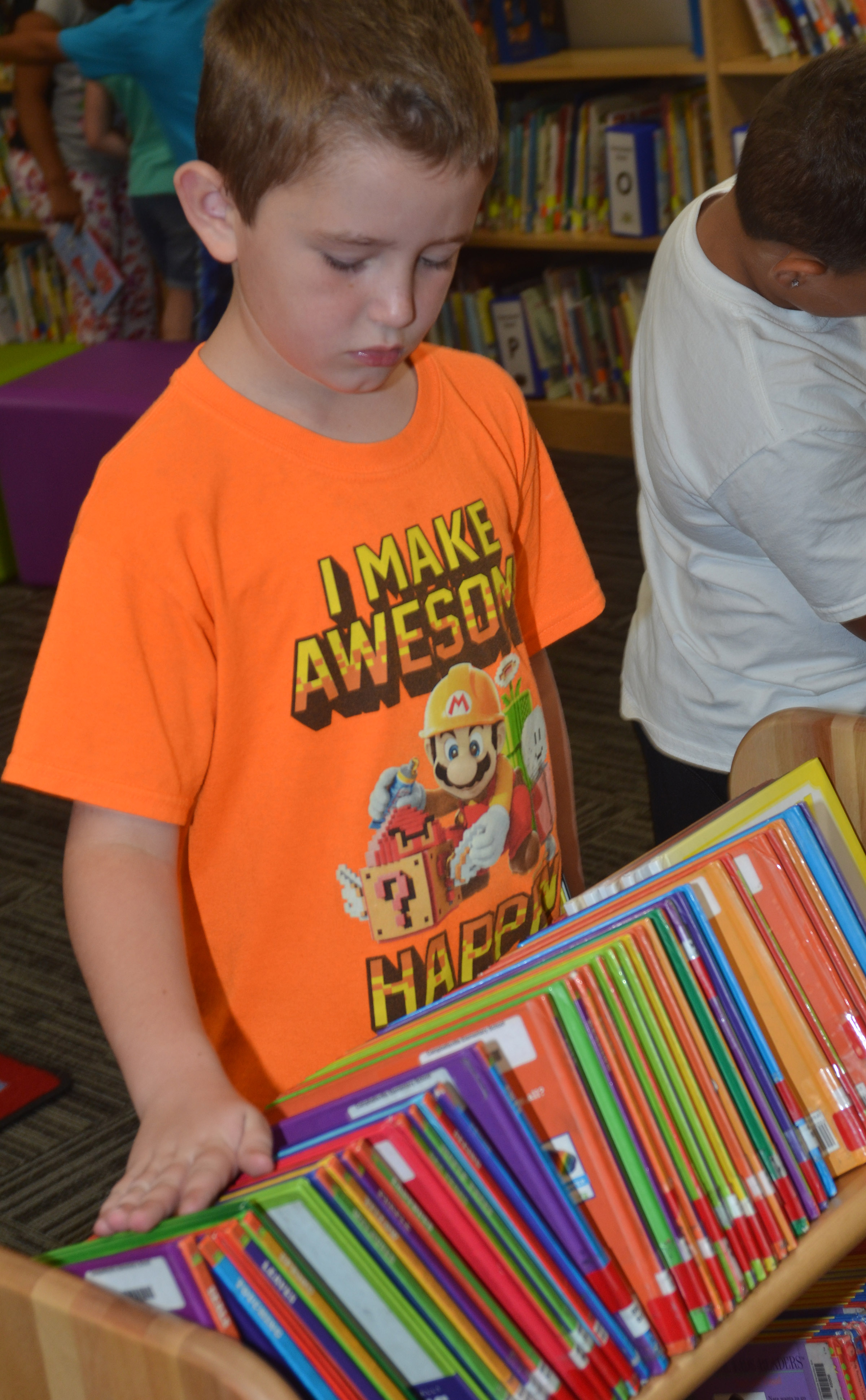 CES second-grader Kevin Bradfield looks through books.