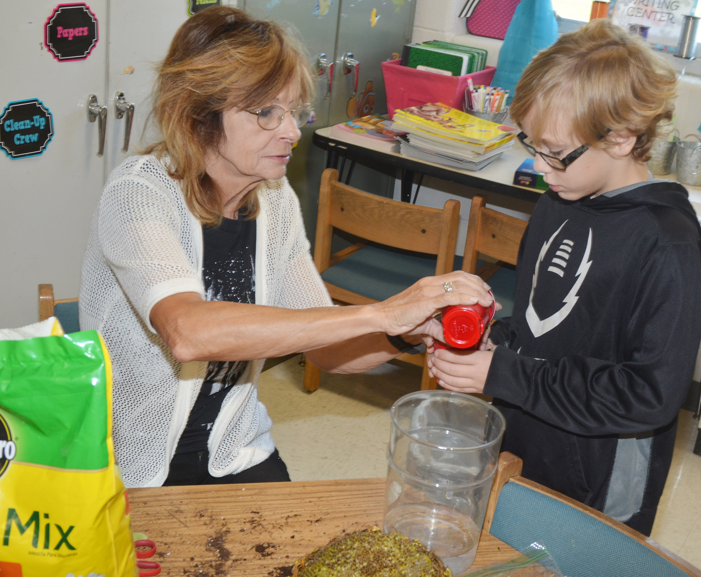 CES third-grade teacher Marcia Sharp helps Adam Edmonds plant his lima bean, which sprouted.