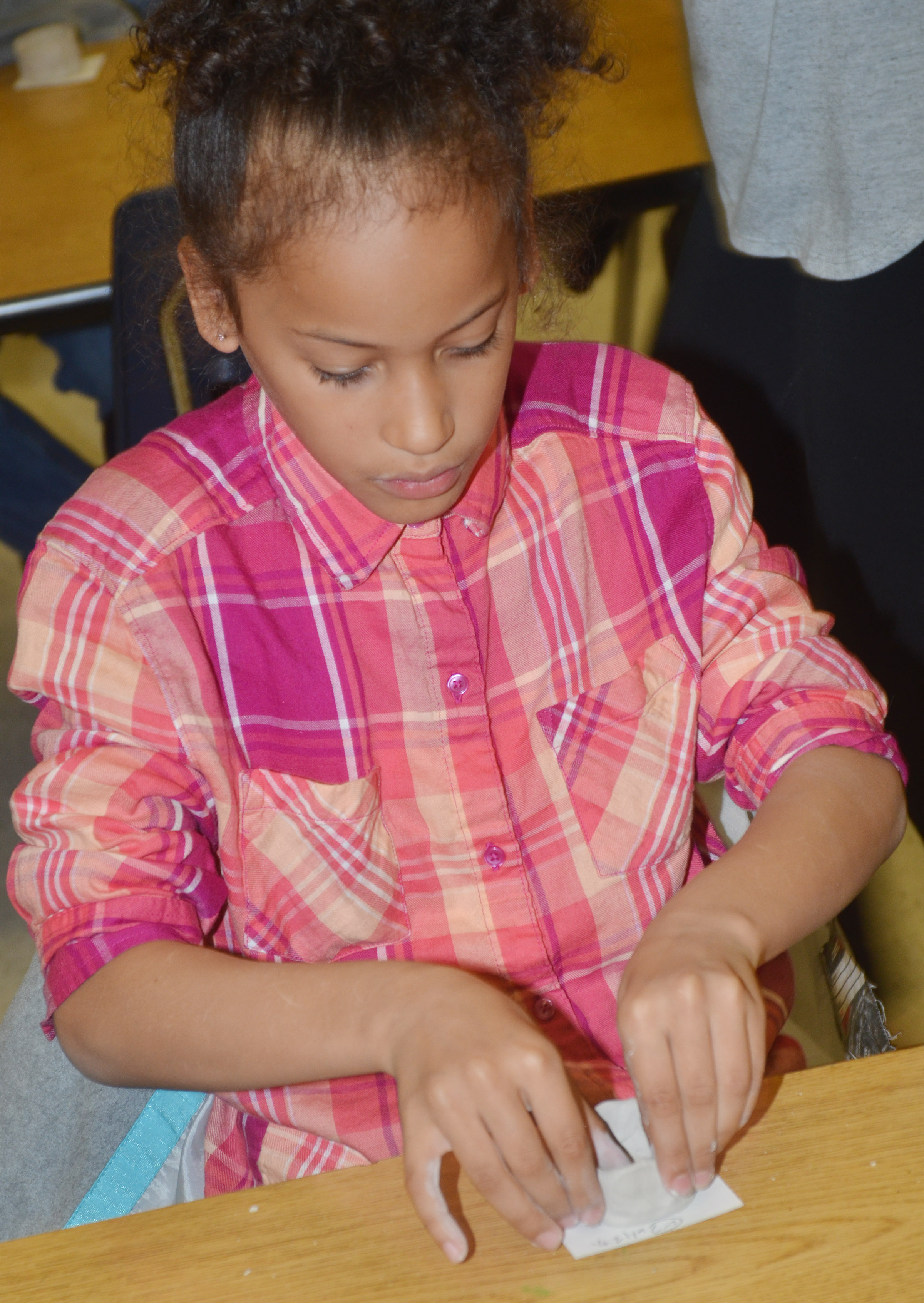 CES second-grader Yazlyn Sutton shapes her pot.