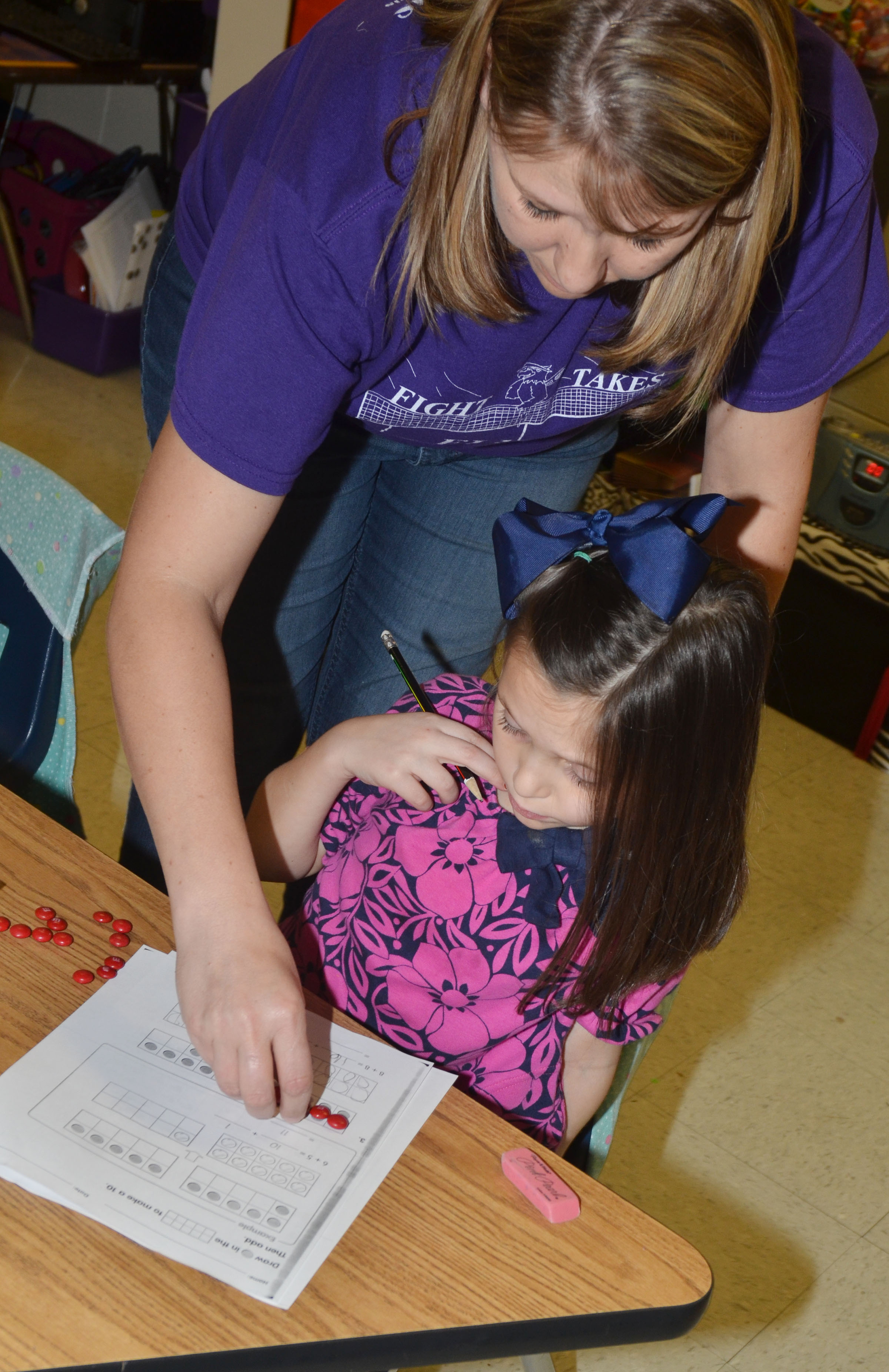 CES first-grade teacher Amanda Greer helps student Serenity Taylor count with her M&Ms.