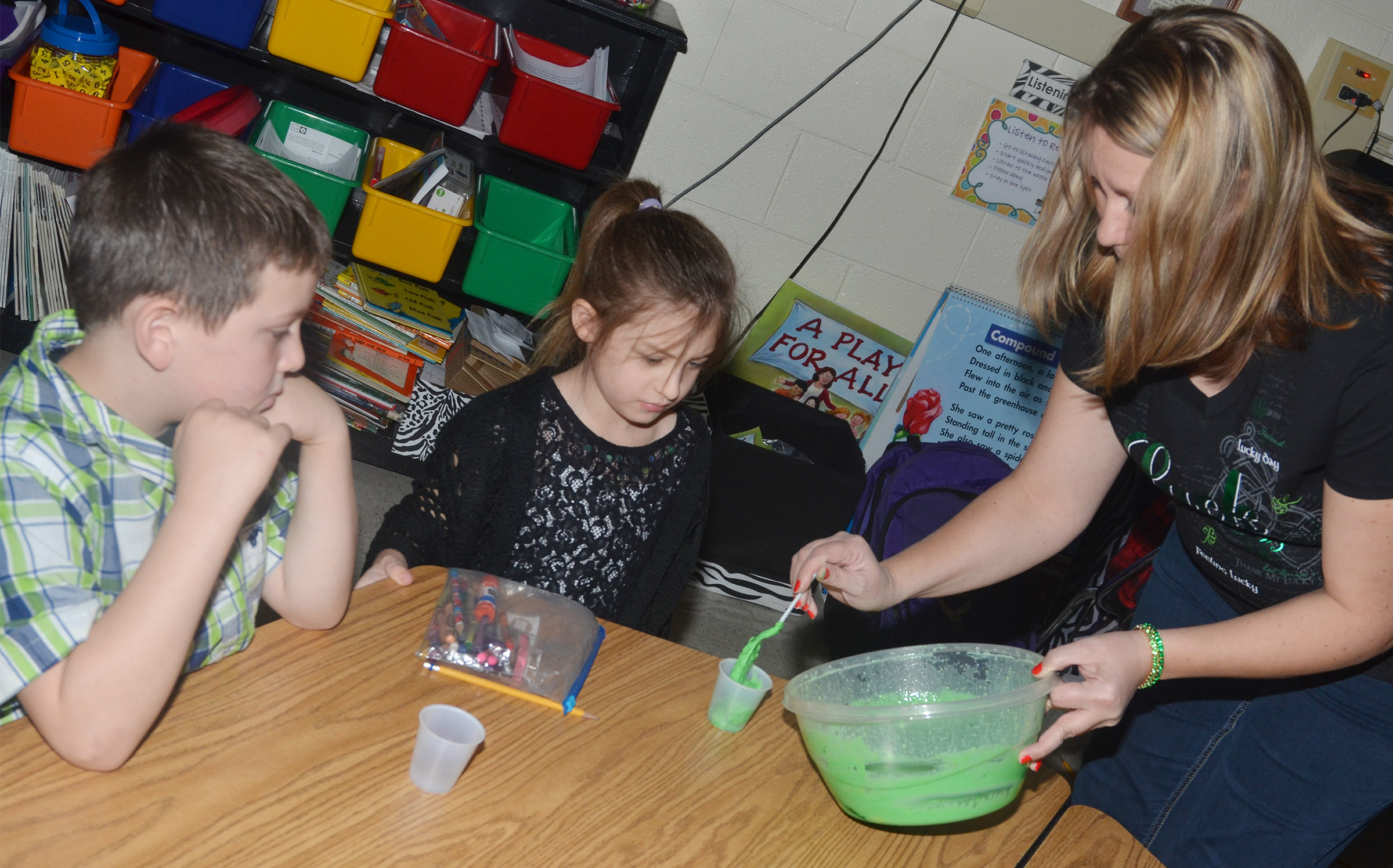 CES first-grade teacher Amanda Greer serves Alexis Mann some pudding.