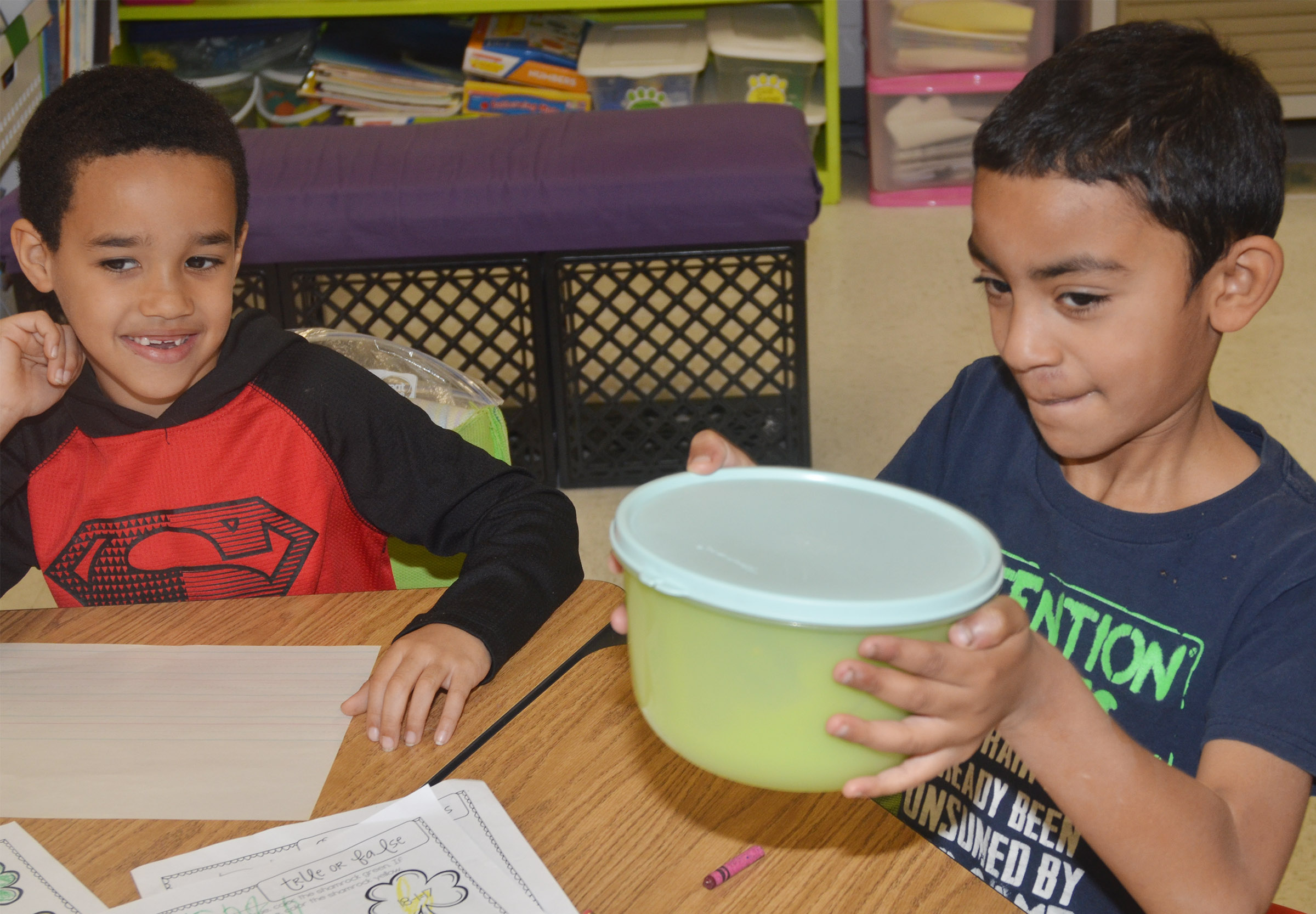CES first-grader Enoch Smith shakes the class's pudding mixture, as Austin Hamilton waits his turn.