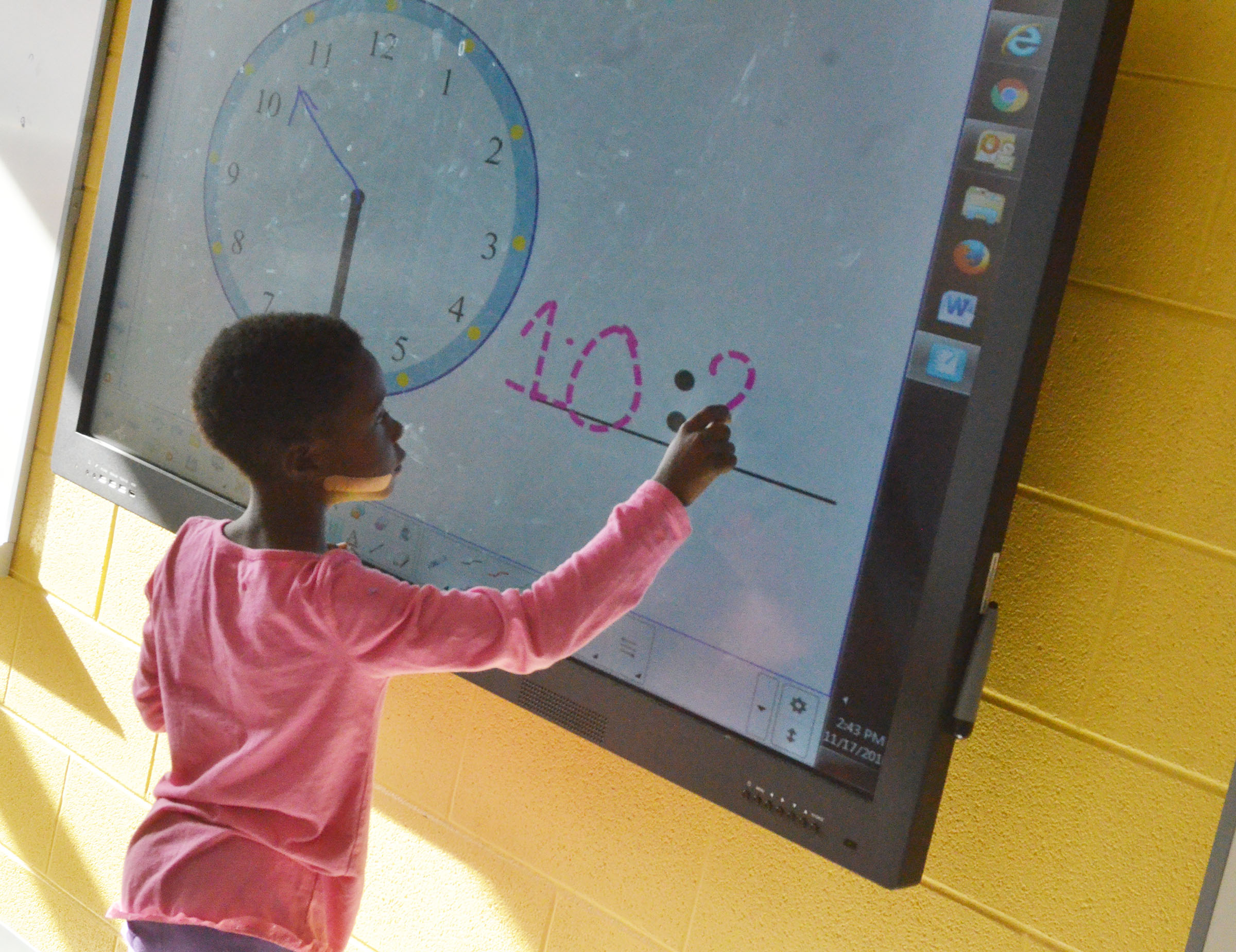 CES first-grader Zion Mitchell writes the time.