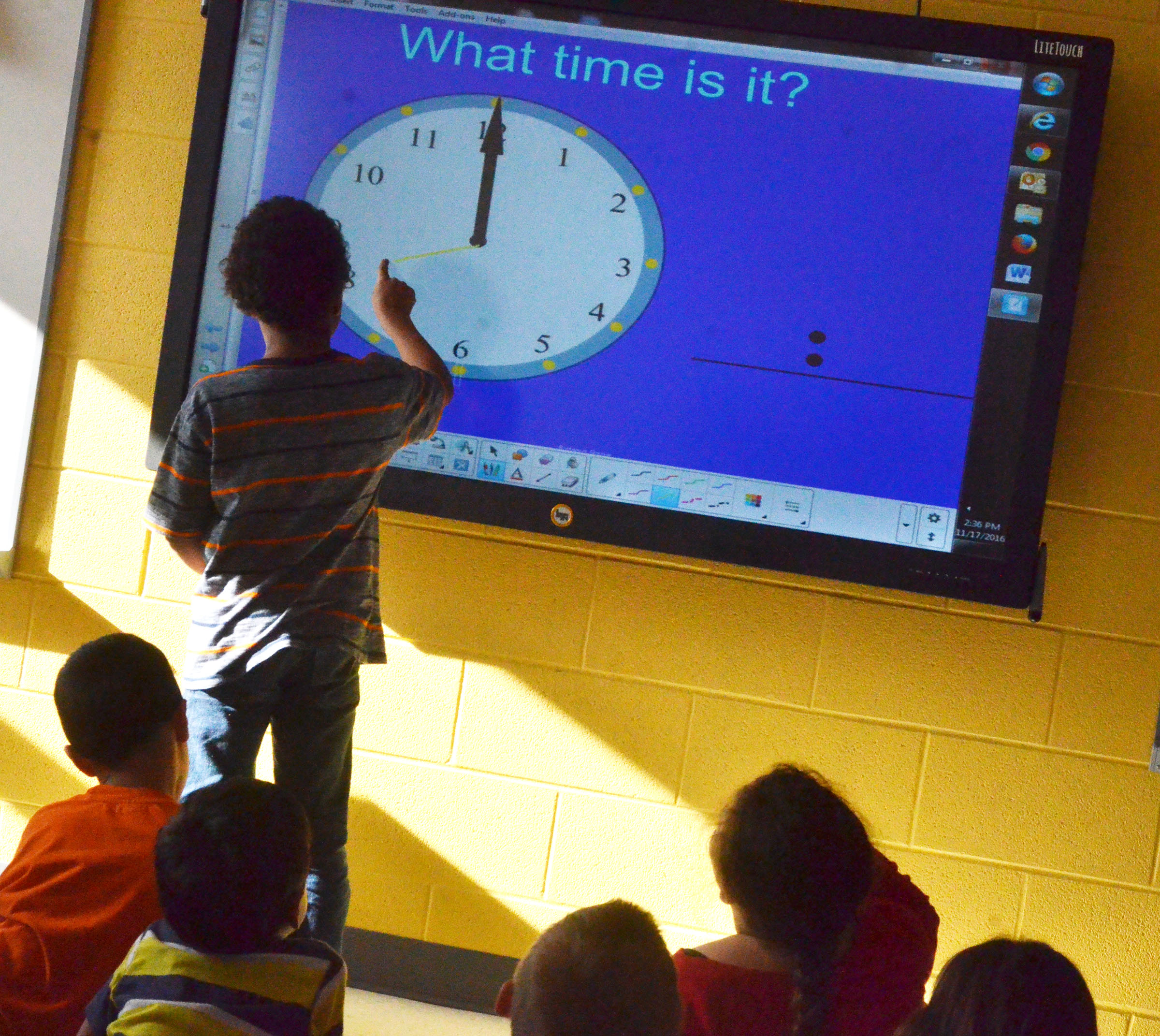 CES first-grader Romeo Goins draws the time and then picks a classmate to tell what time he drew.