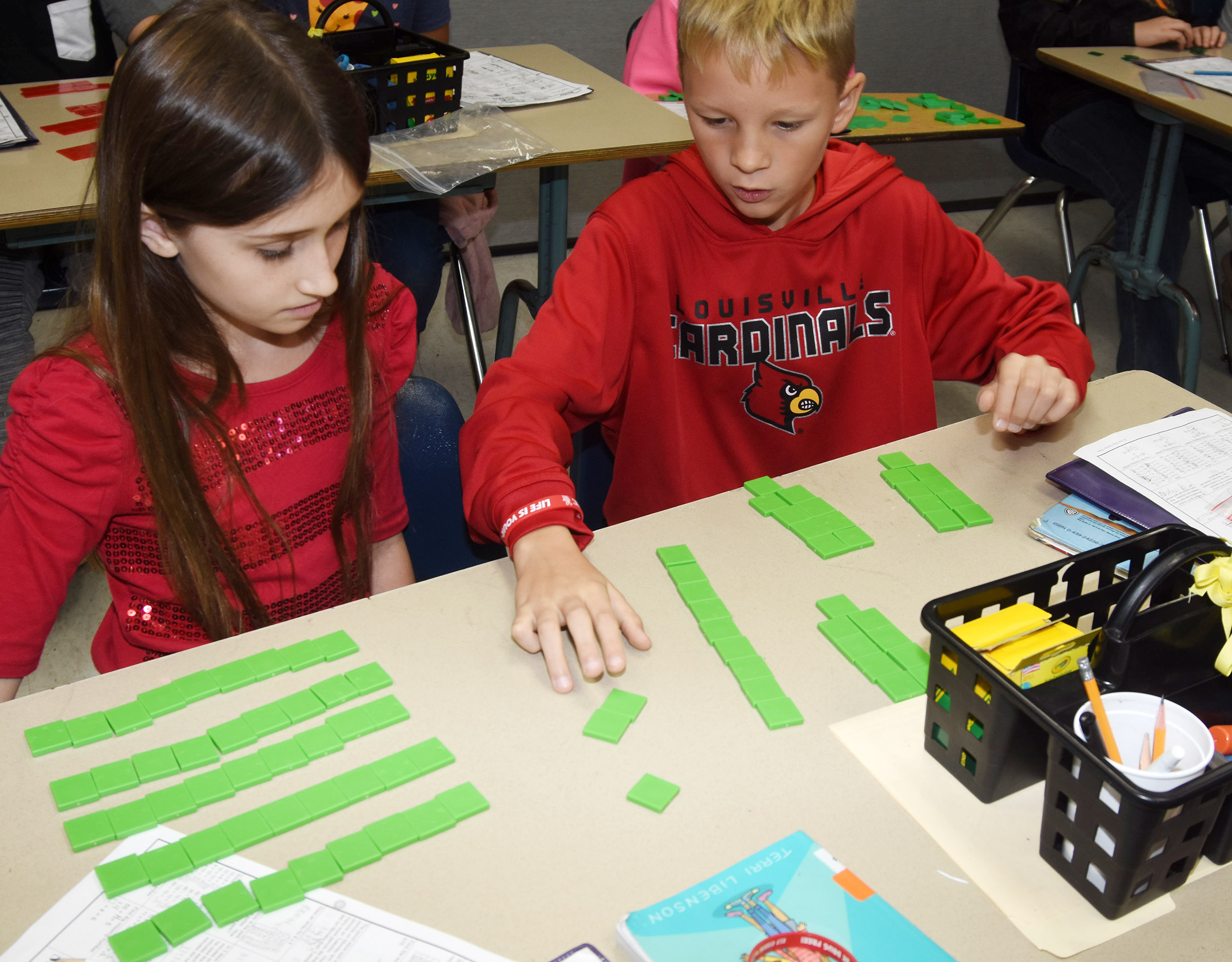 CES fourth-graders Cadence Burton, at left, and Braxton Agee work a division problem with blocks.