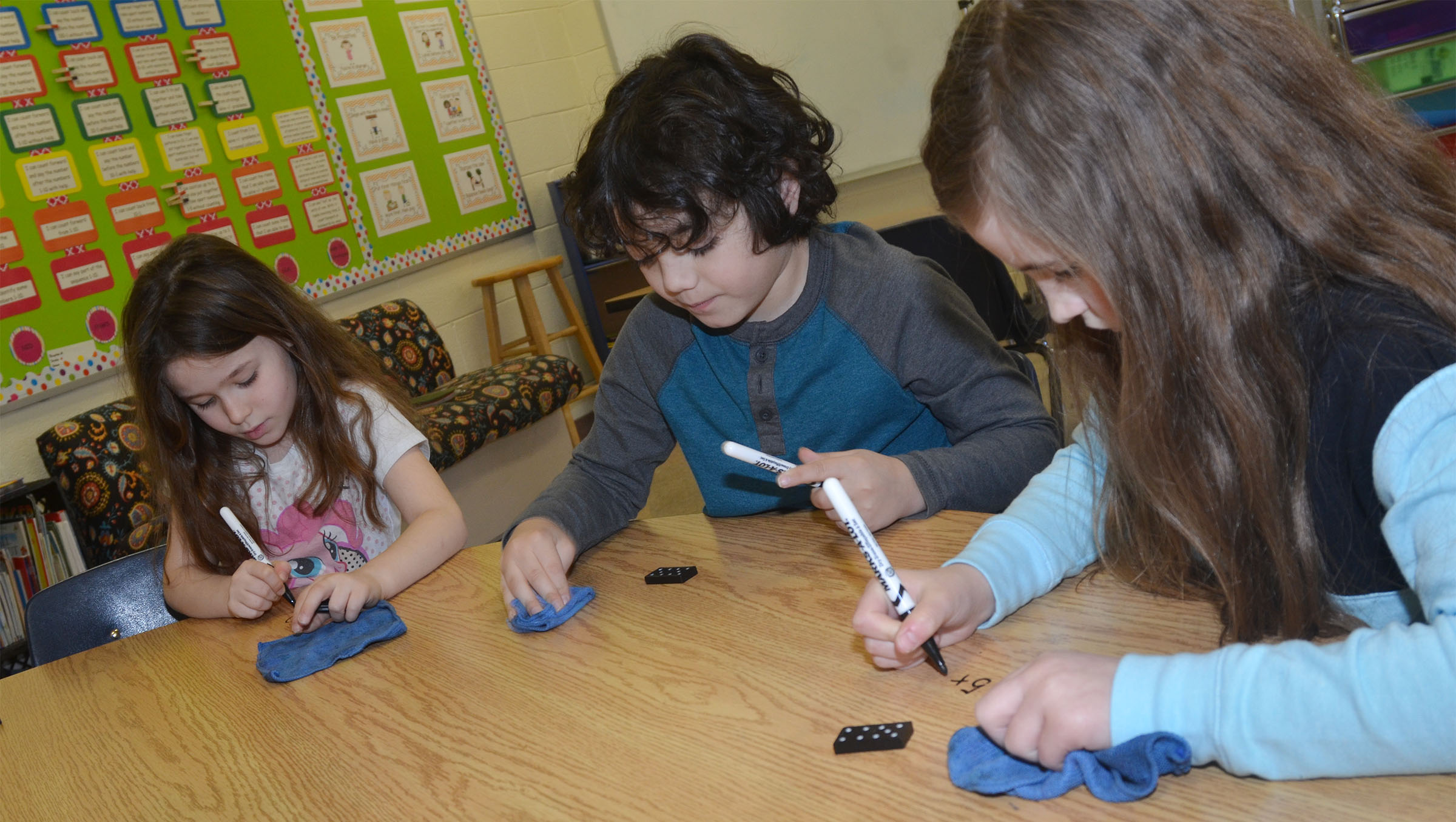 CES first-graders, from left, Giselle Moreno, Diego Aquino and Alyssa Farmer practice their math skills by playing a Dominos game.