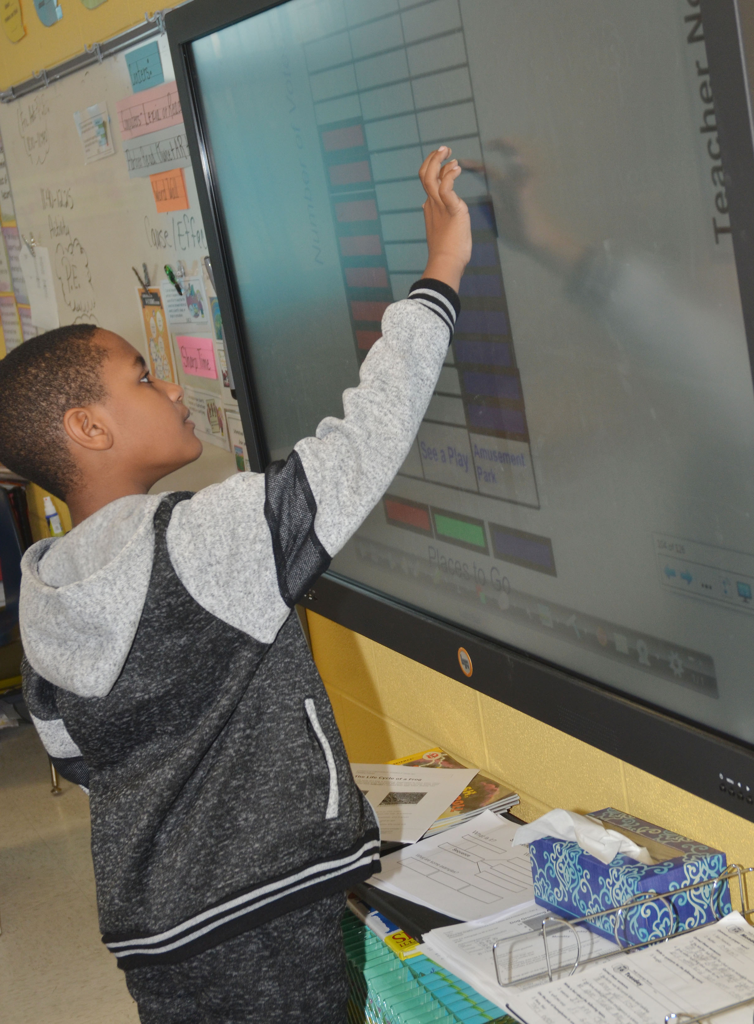 CES third-grader Shaiden Calhoun adds how many students want to go to an amusement park on the class's bar graph.