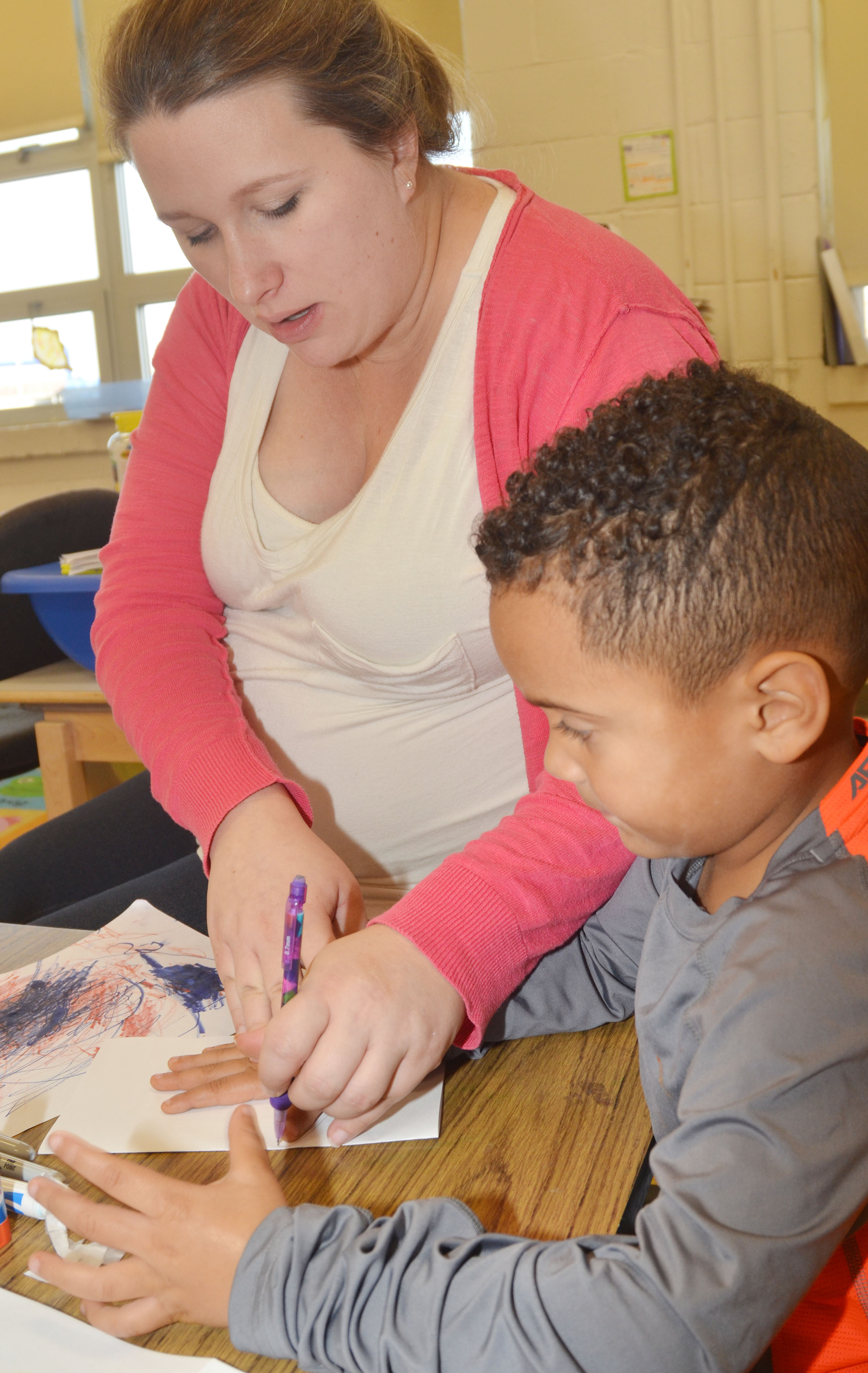 CES preschool assistant Jessica Williams traces Kingston Cowherd's hand for the card he is making for an active duty soldier.