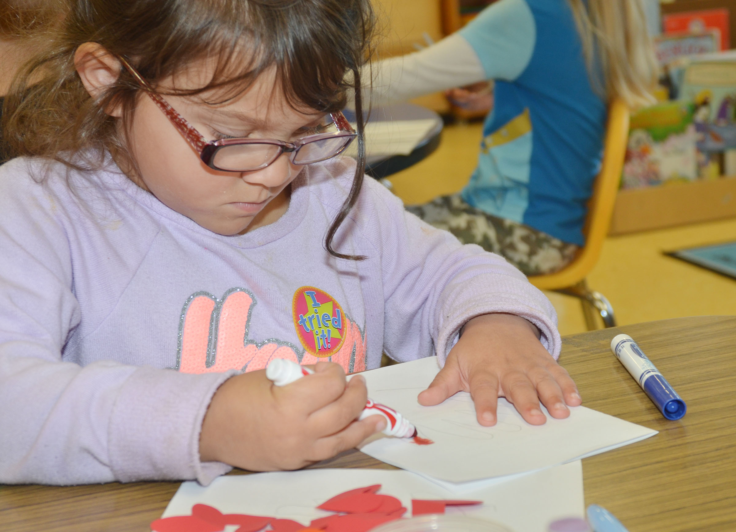 CES preschool student Addisyn Taylor colors a card for an active duty soldier.