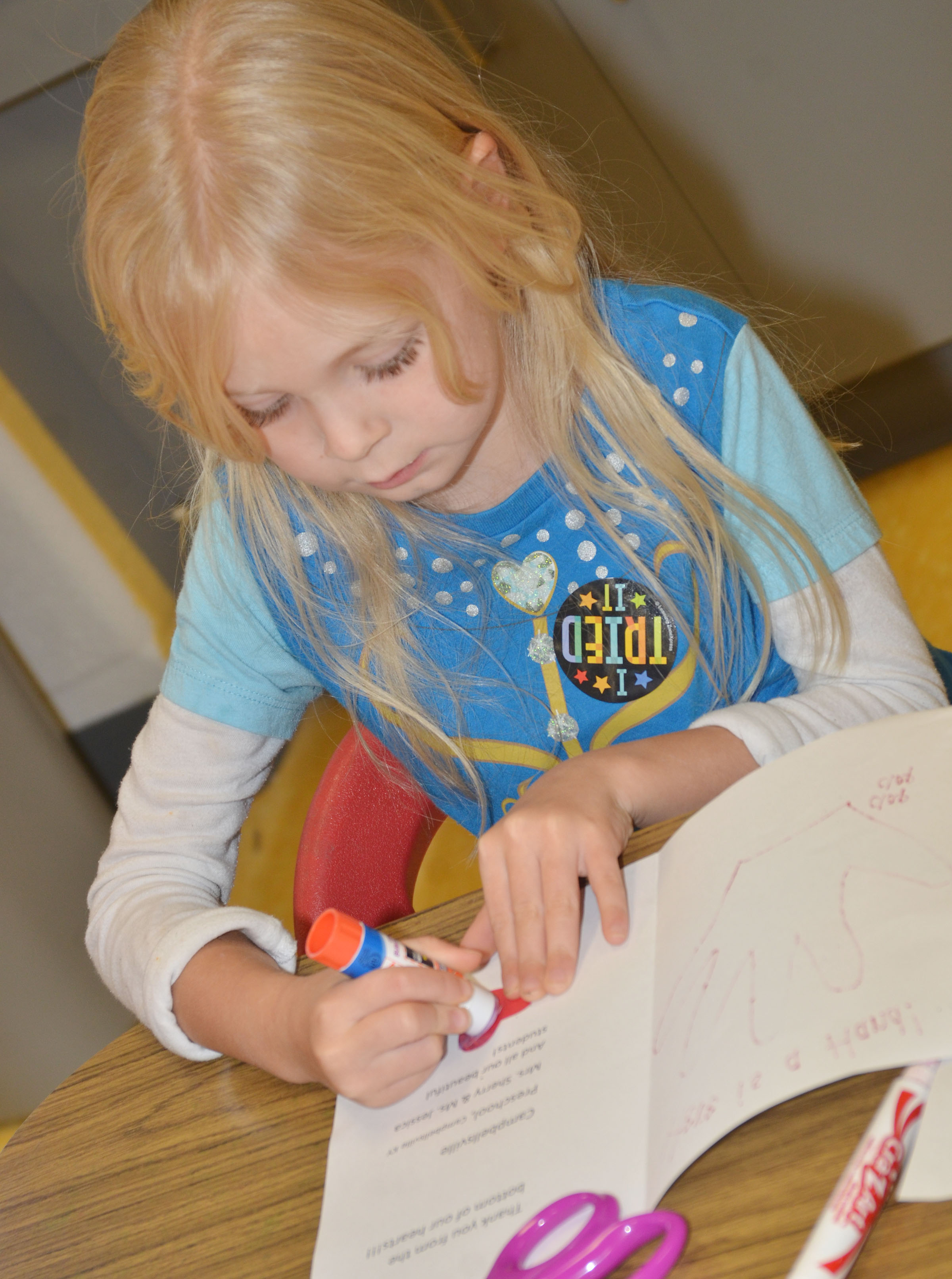 CES preschool student Alinna Bray adds a heart to the card she made for an active duty soldier.