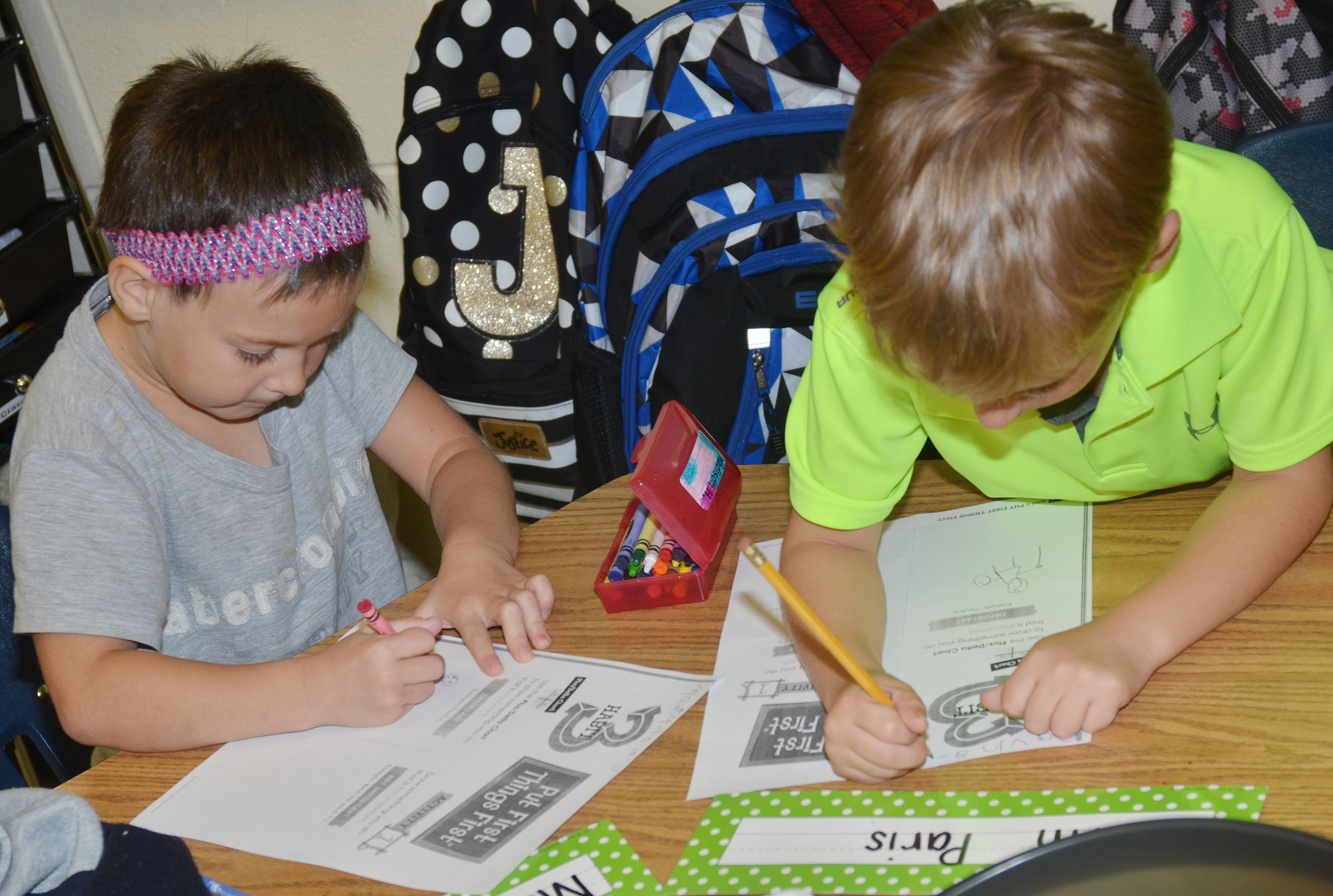 CES first-graders Madison Haywood, at left, and Gavin Paris draw pictures of something that is important.