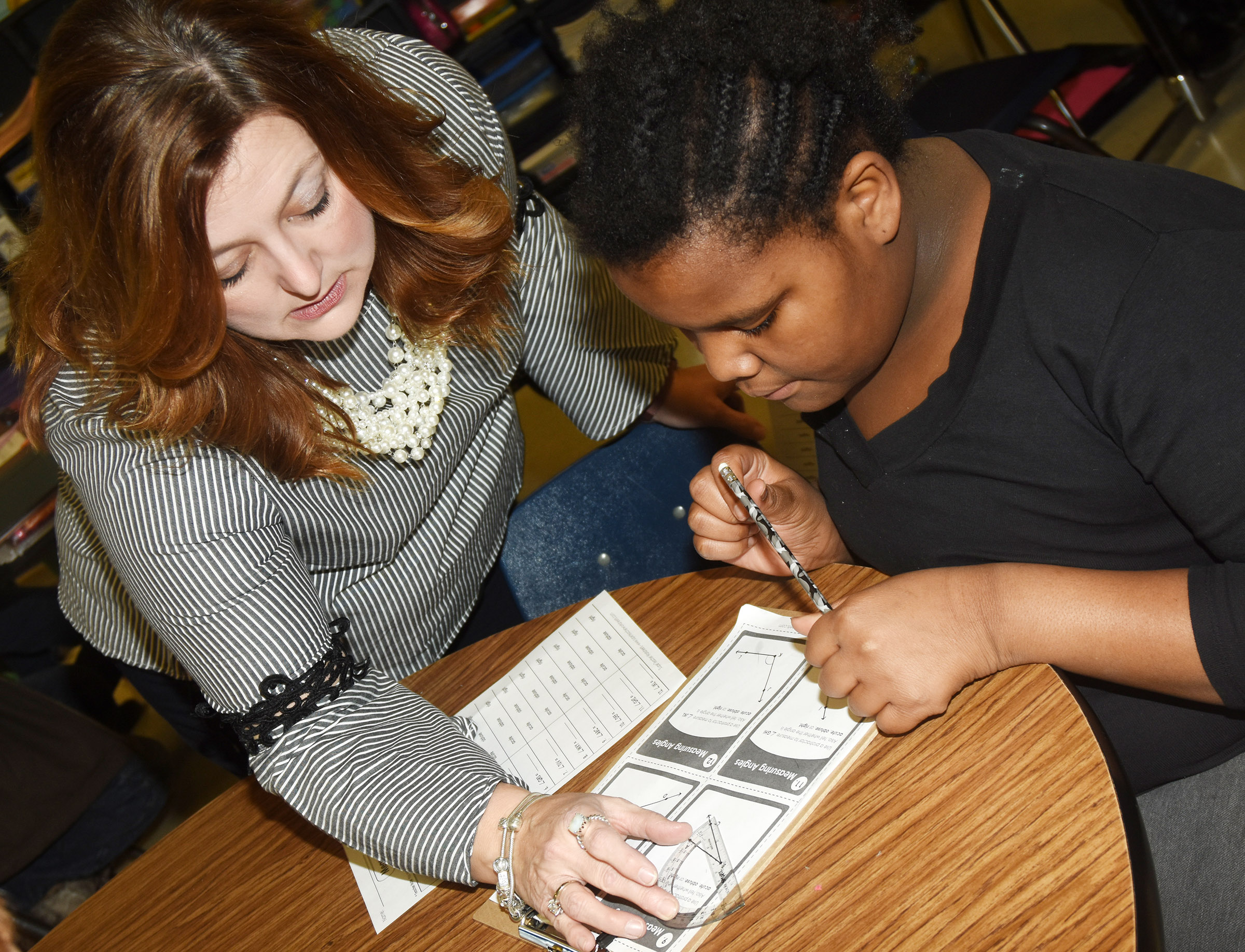 CES fourth-grade teacher Garnetta Murrell helps Talaysia Daniels measure an angle.