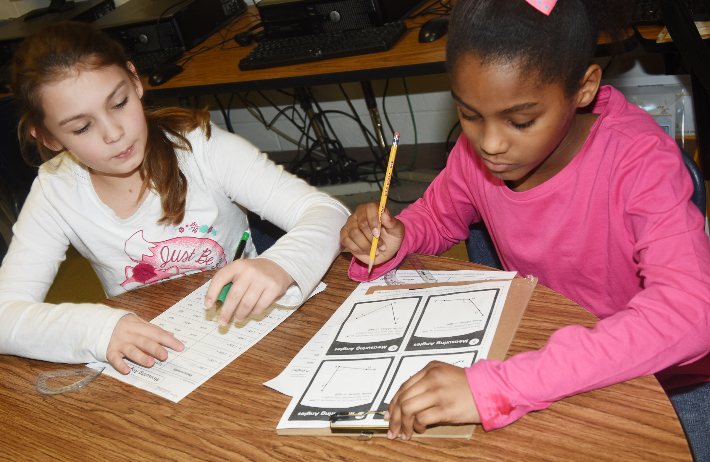 CES fourth-graders Kealey Mann, at left, and Maliyah Harris work together to measure angles.