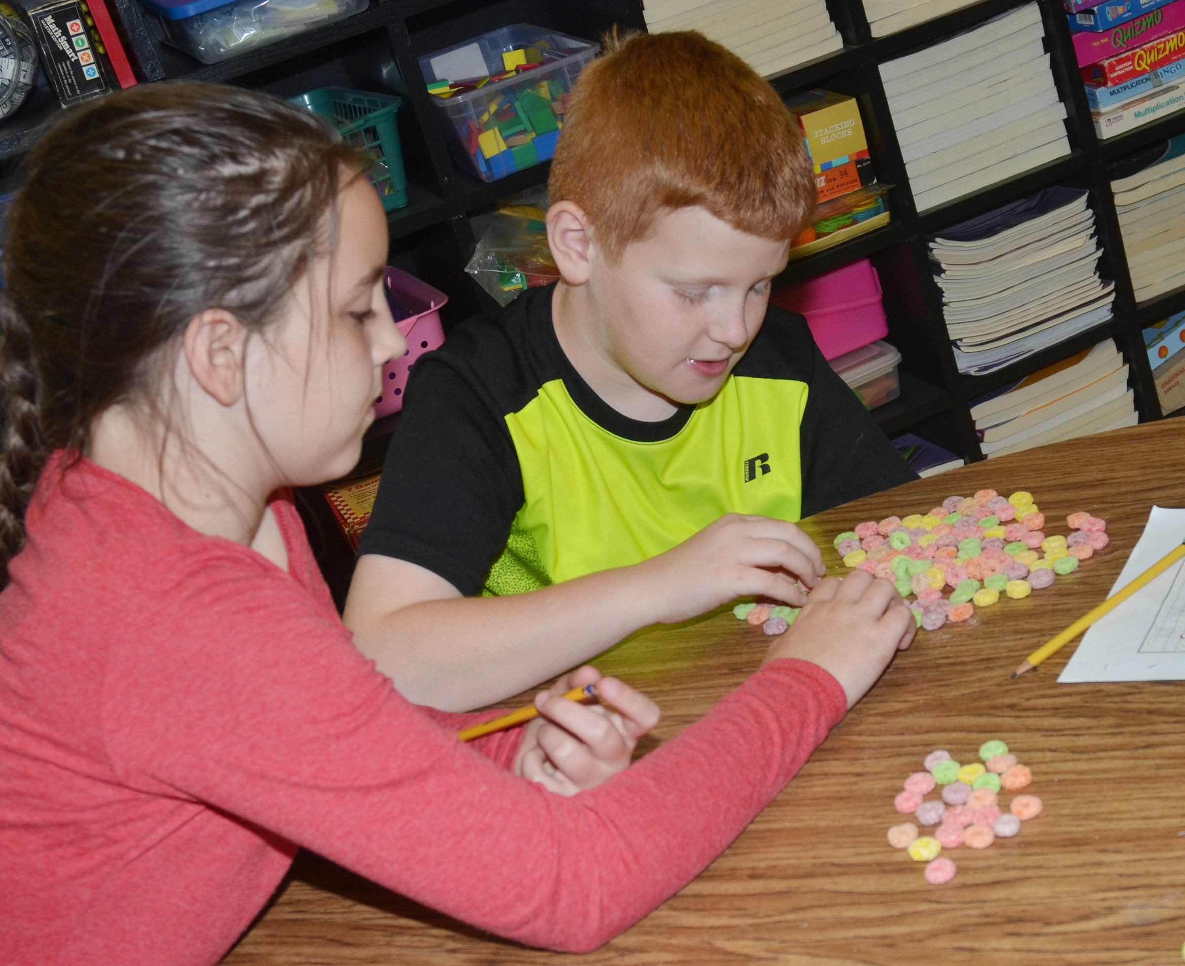 CES fourth-graders Alexis Roddy, at left, and Westin Dudgeon count using cereal.