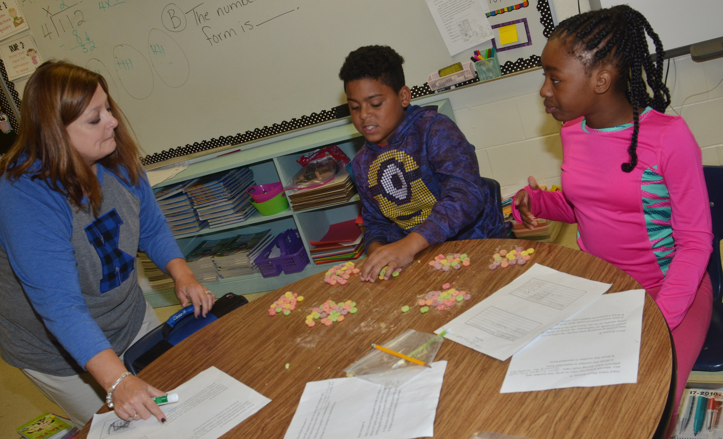 CES fourth-grade math teacher Garnetta Murrell helps students Bryson Groves, center, and Tiffani Gaddie count using pieces of cereal.
